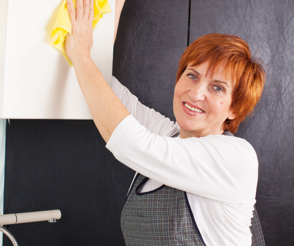 Woman cleaning kitchen cabinet with yellow rag