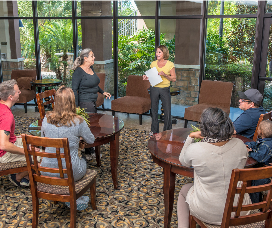 Small group attending a presentation inside a building with a scenic view