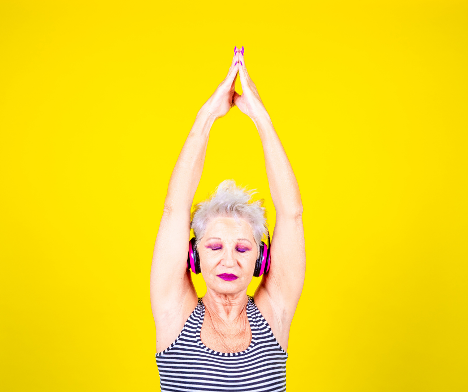 Woman in a relaxing stance with earphones and hands raised above head