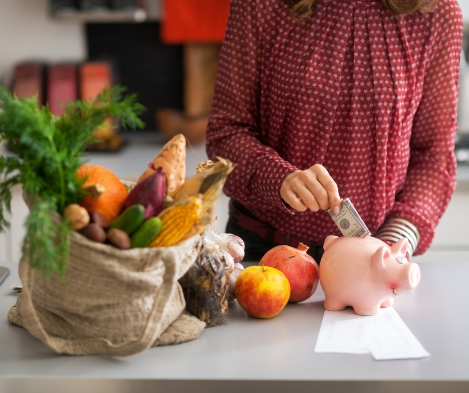 Woman adding money to piggy bank, grocery purchases on counter