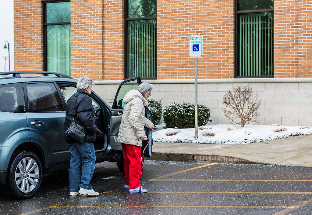 elderly woman and helper walking on icy parking lot