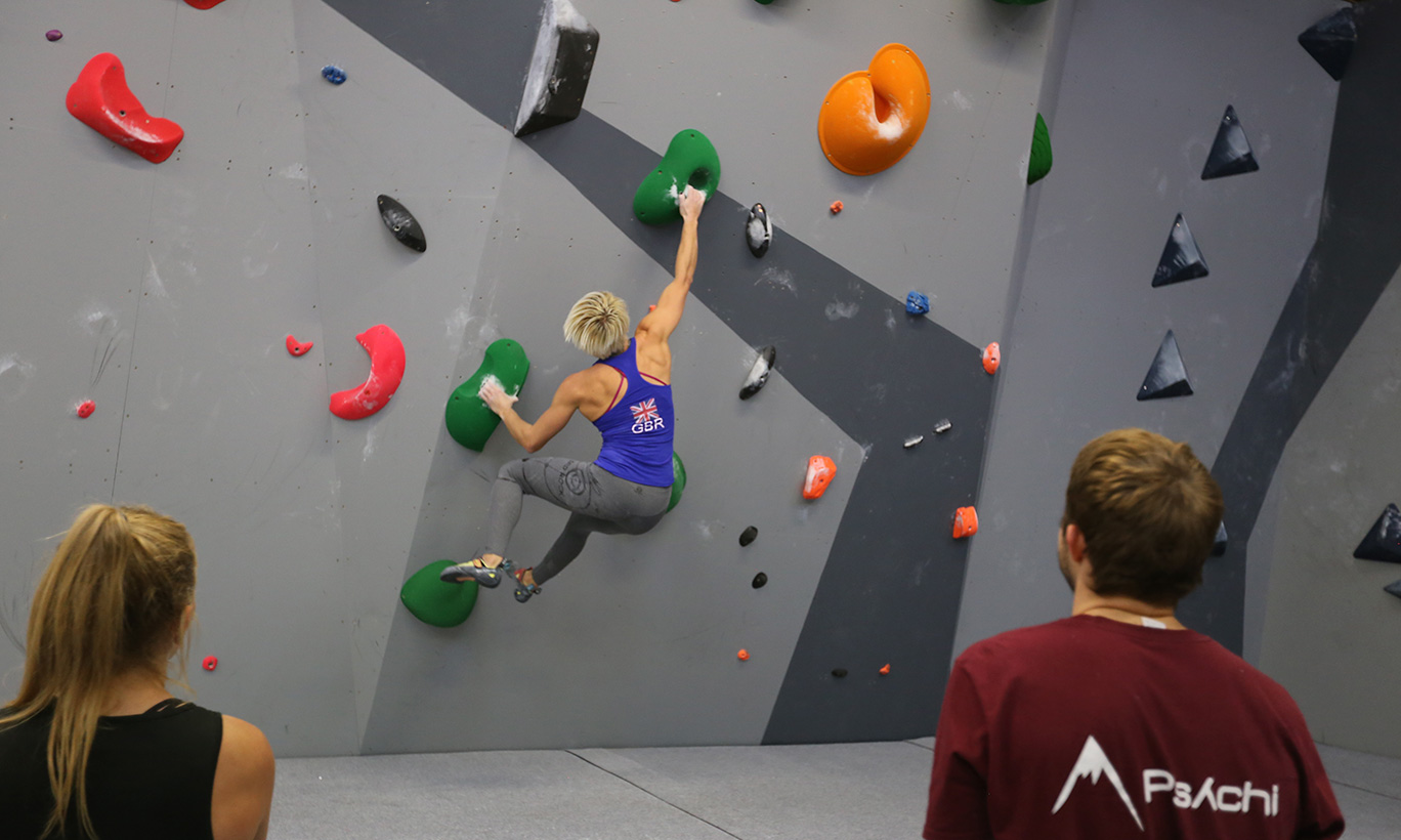 A photo of a woman bouldering in the climbing centre