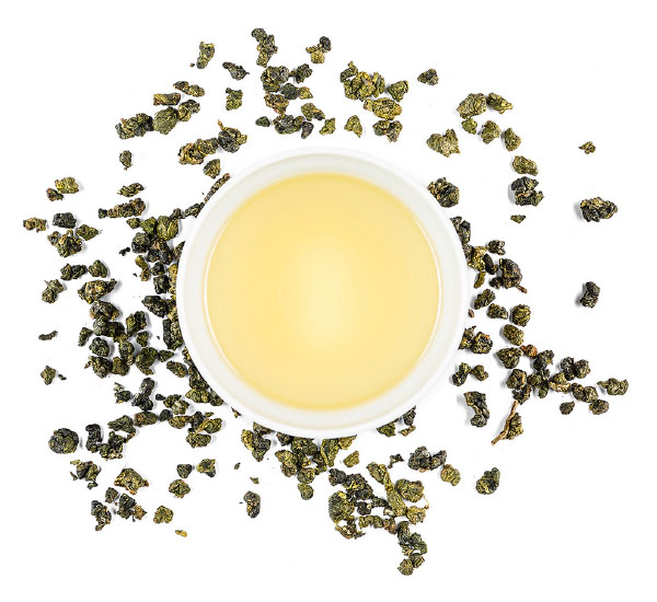 Cup of loose leaf tea with tea leaves surround it.