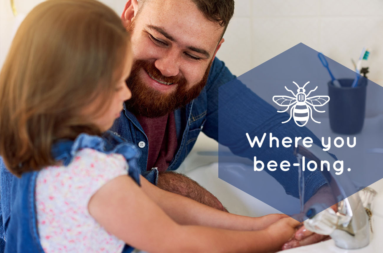 Photo of a father and daughter with the Onward Homes Manchester bee branding