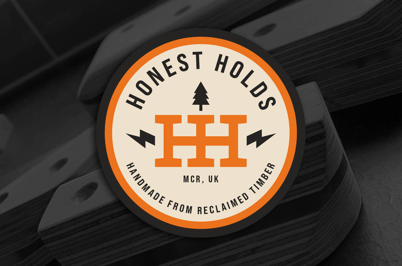 Honest Holds logo with climbing holds in the background