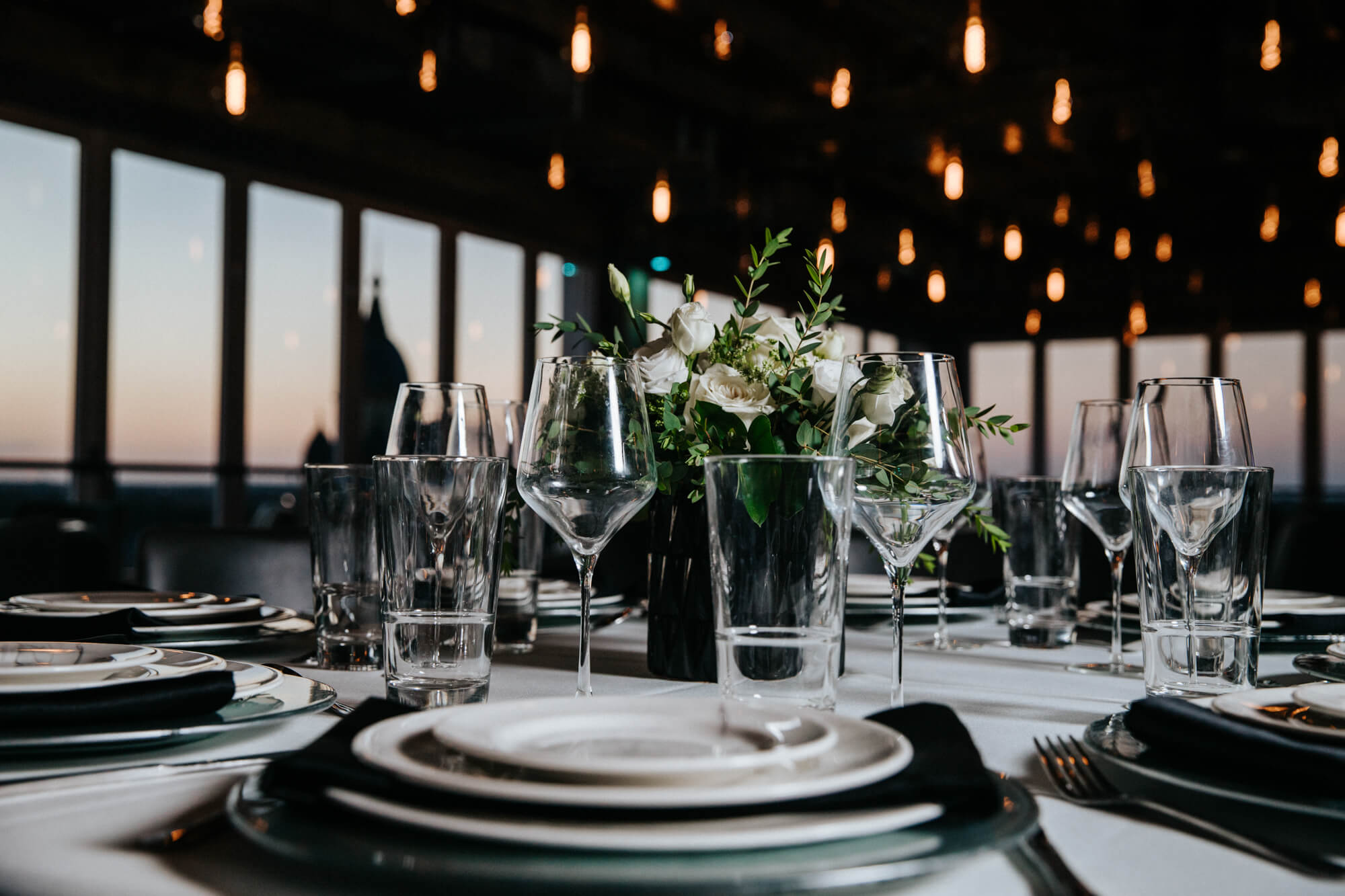 Place settings and beautiful rose bouquets showcase Sunago Bell's potential for events. In the background, you see the twinkling Edison bulbs and a blurred view of the Downtown Denton Square.
