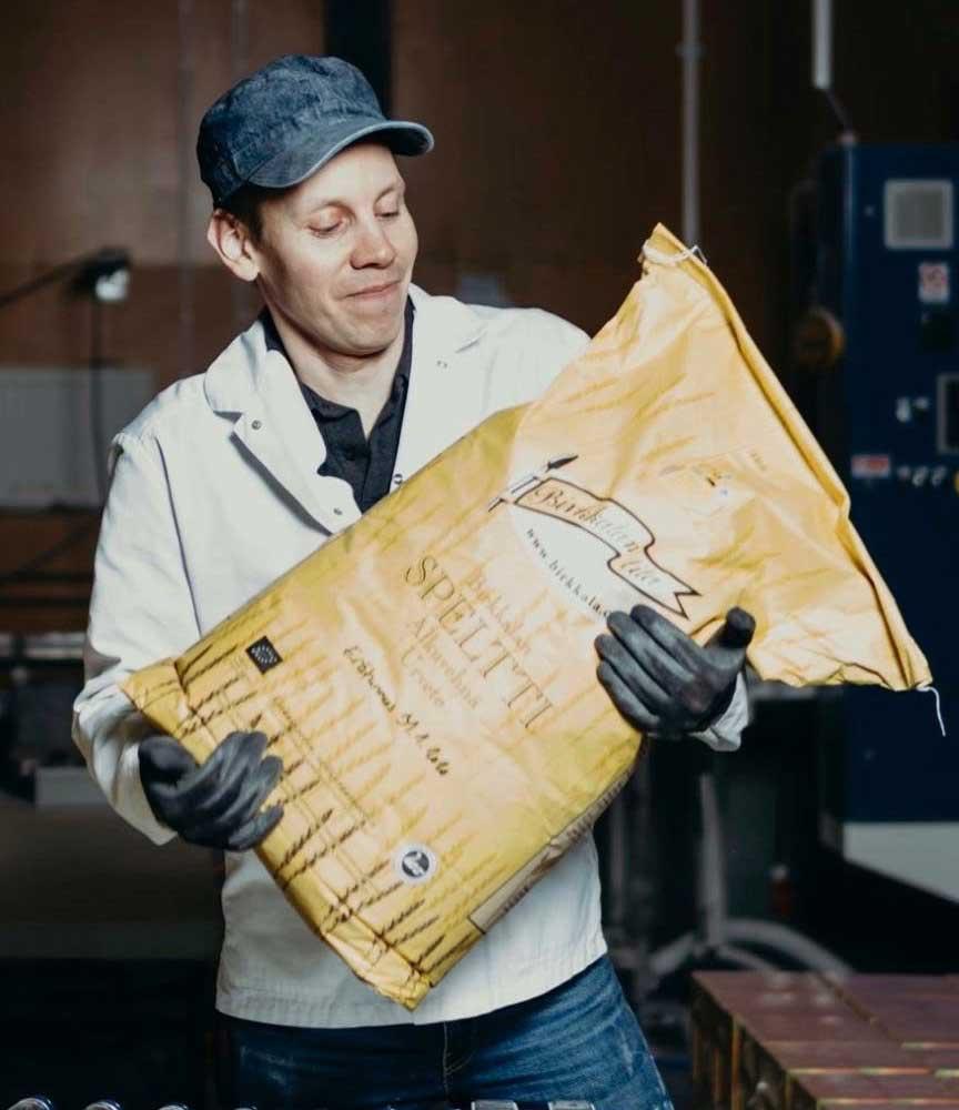 Simo töissä Birkkalan myllyllä nostelemassa spelttisäkkejä
