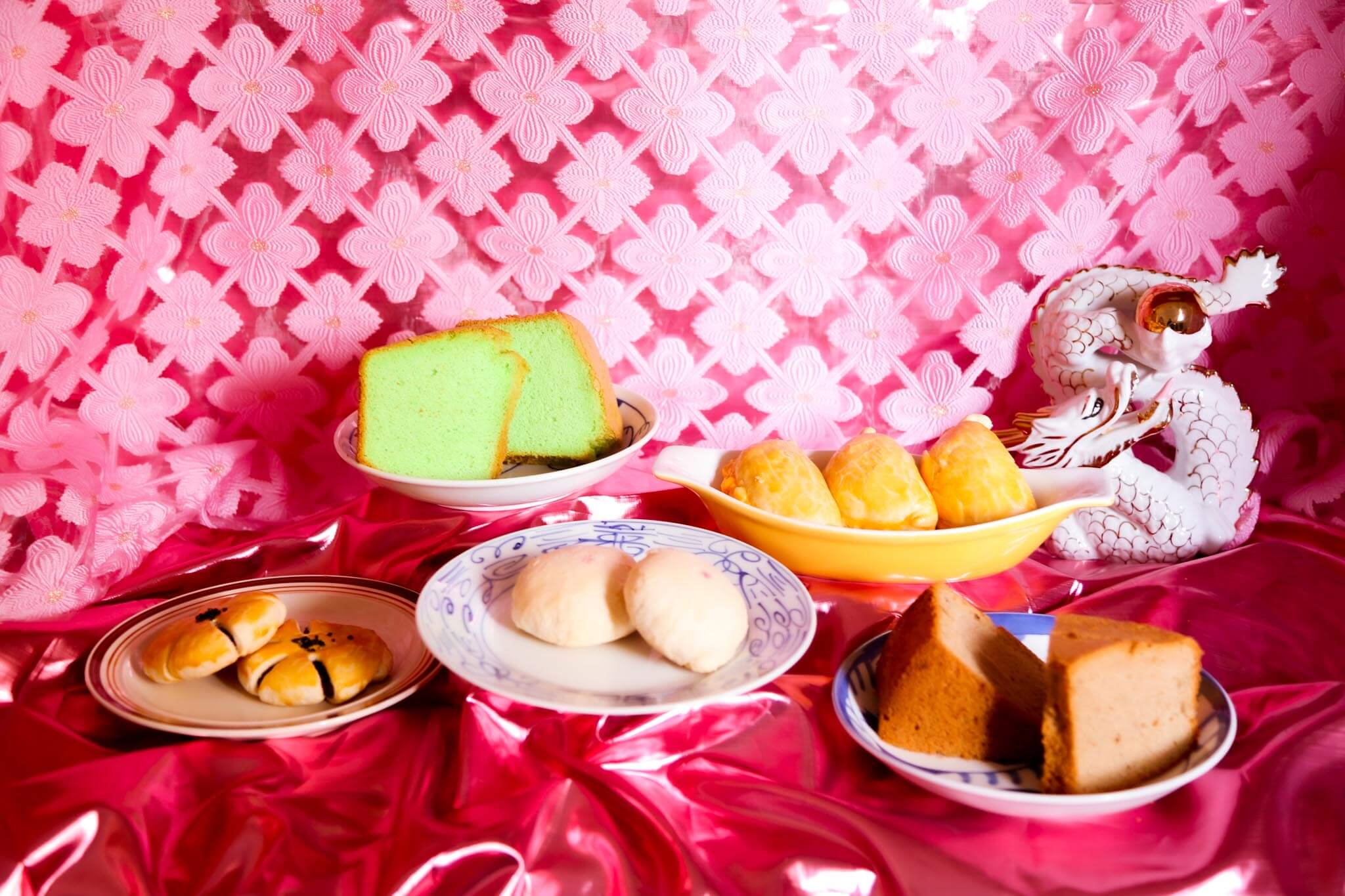 Image of variety of Chinese-Malaysian pastries beautifully plated with a bright pink cloth background