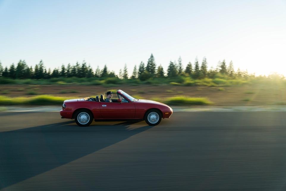 Rotes Cabrio auf einer Landstraße mit Bäumen im Hintergrund