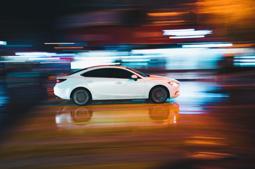 Weißes Auto vor verschwommenem Hintergrund