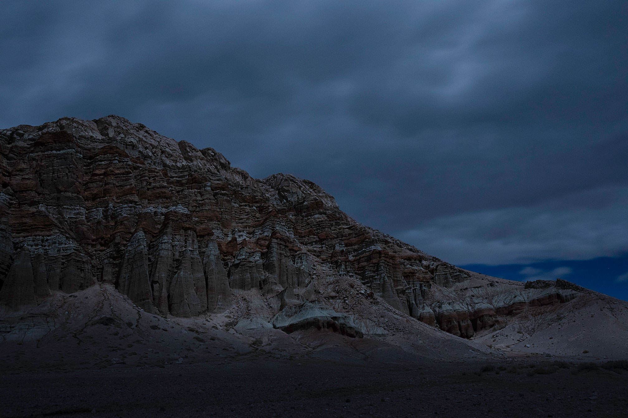 Eroded cliffs under a cloudy night sky.