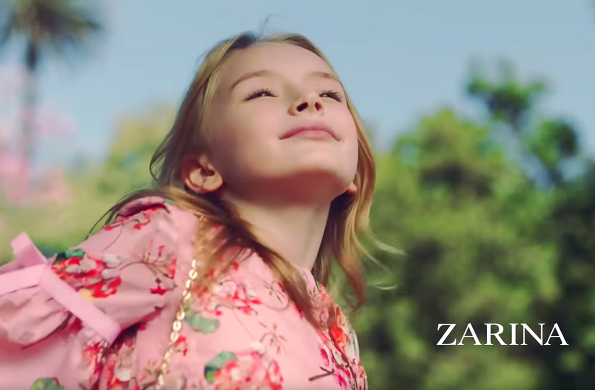 Кадр из рекламы ZARINA с девочкой в платье с цветами на фоне неба и деревьев