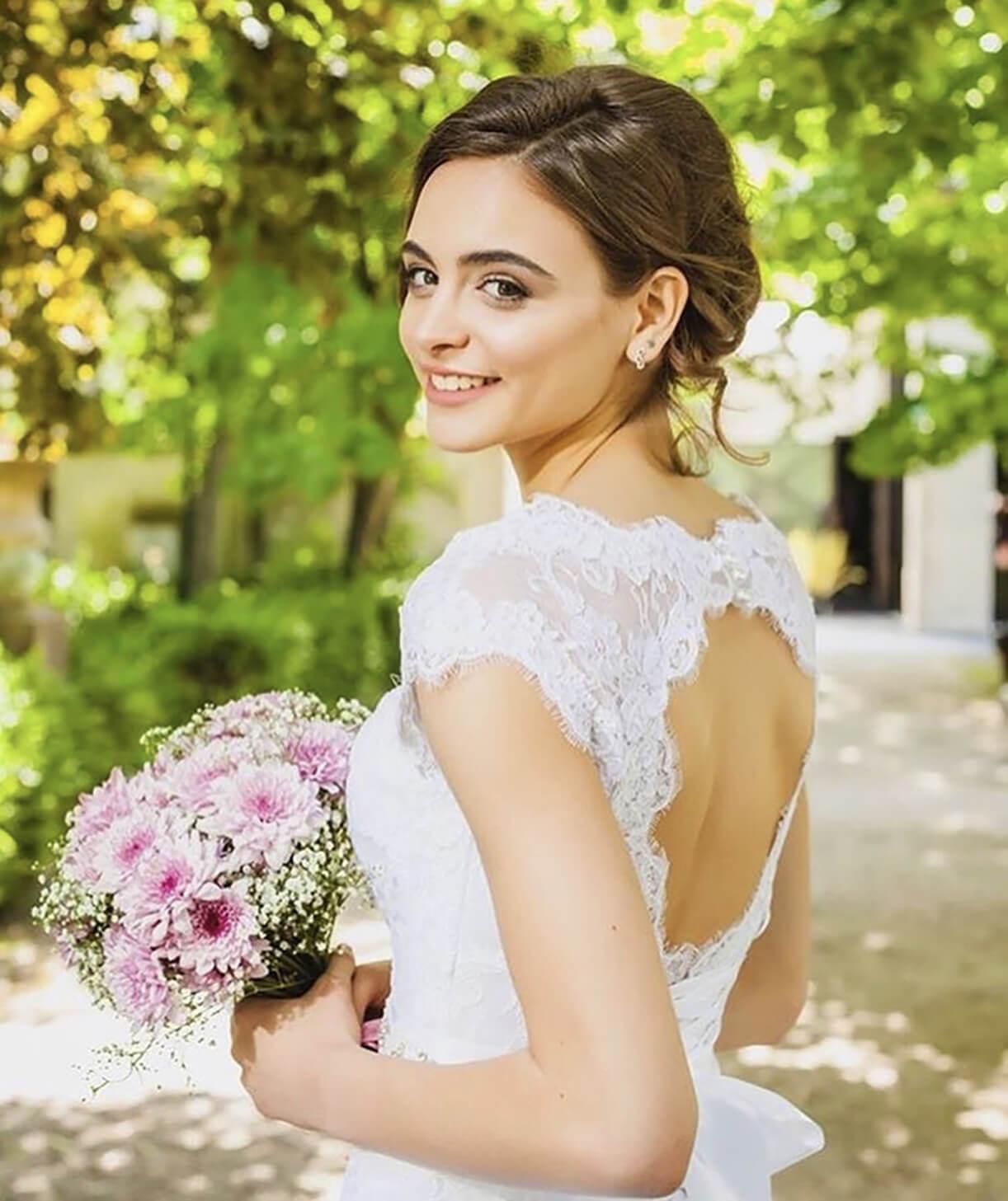 Девушка в свадебном образе с макияжем и букетом в парке