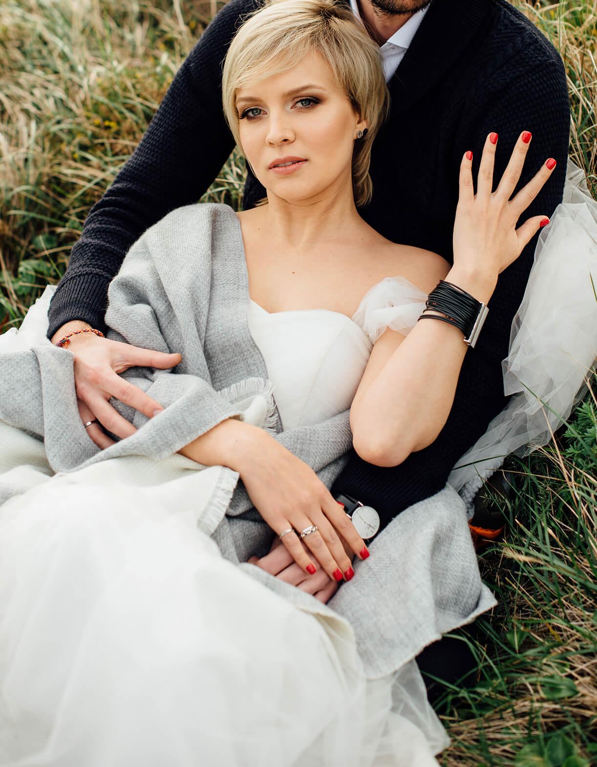 Невеста в объятиях жениха на траве. Свадебный макияж