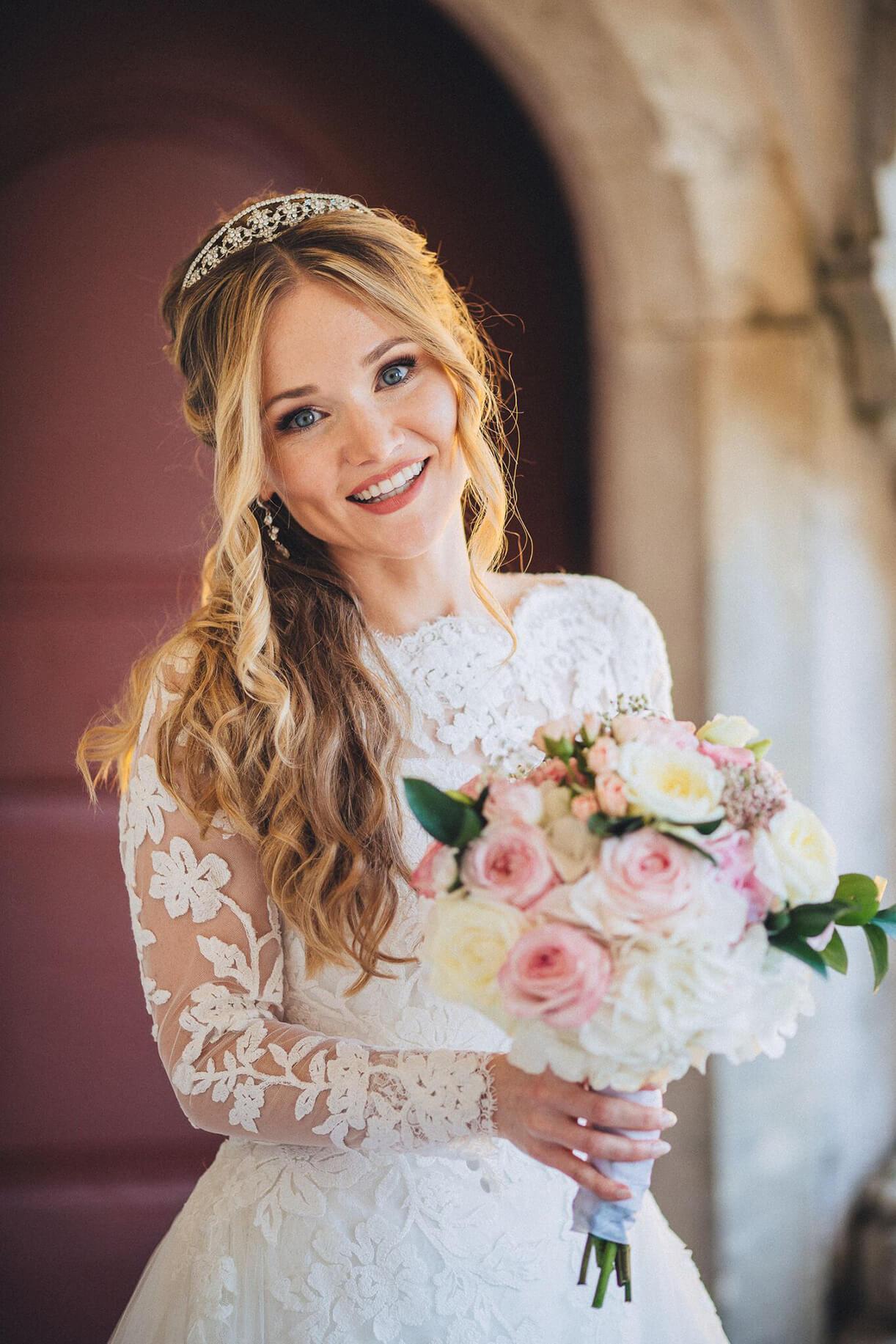 Невеста в свадебном образе с букетом на фоне