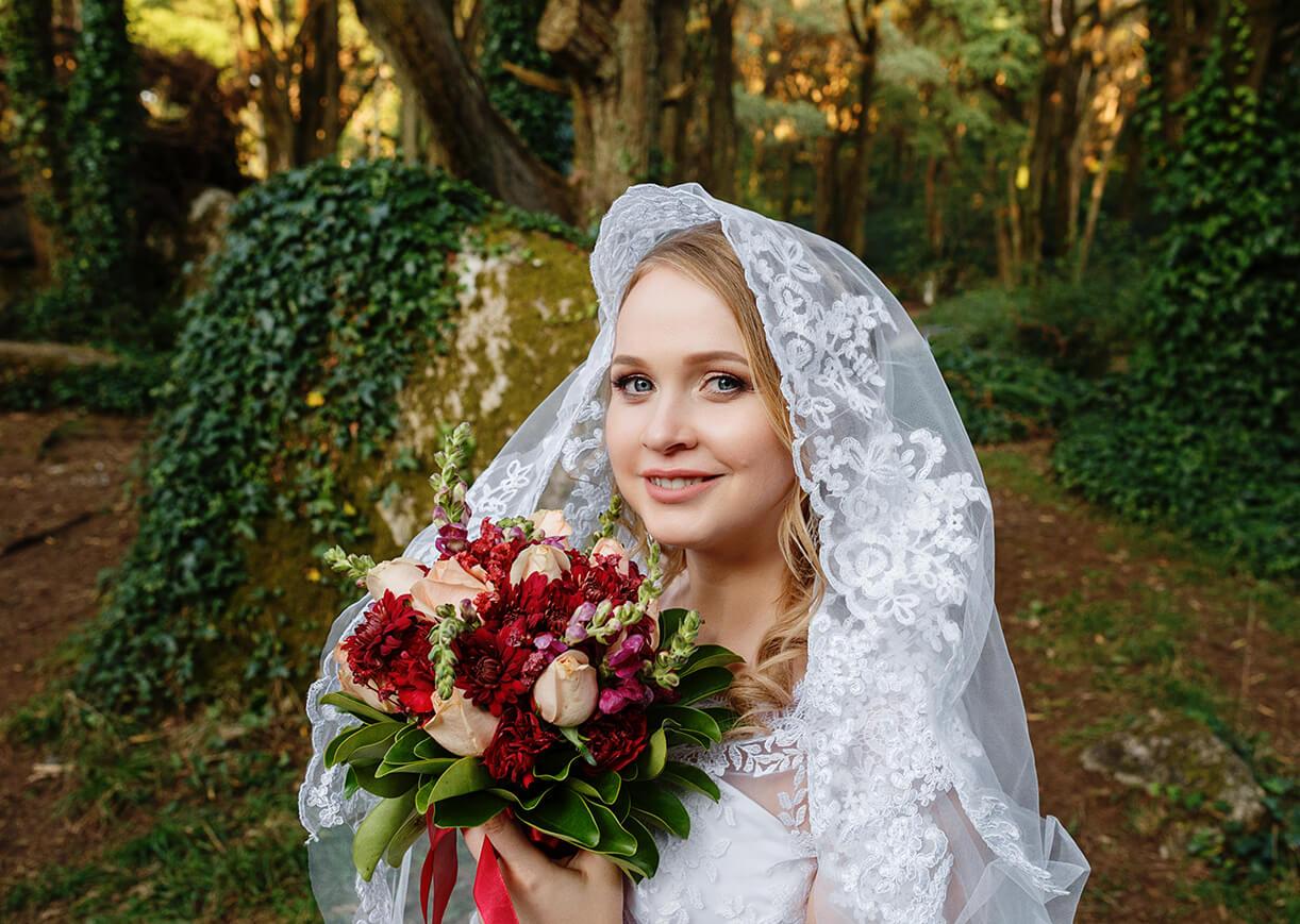 Невеста в фате с букетом в лесу