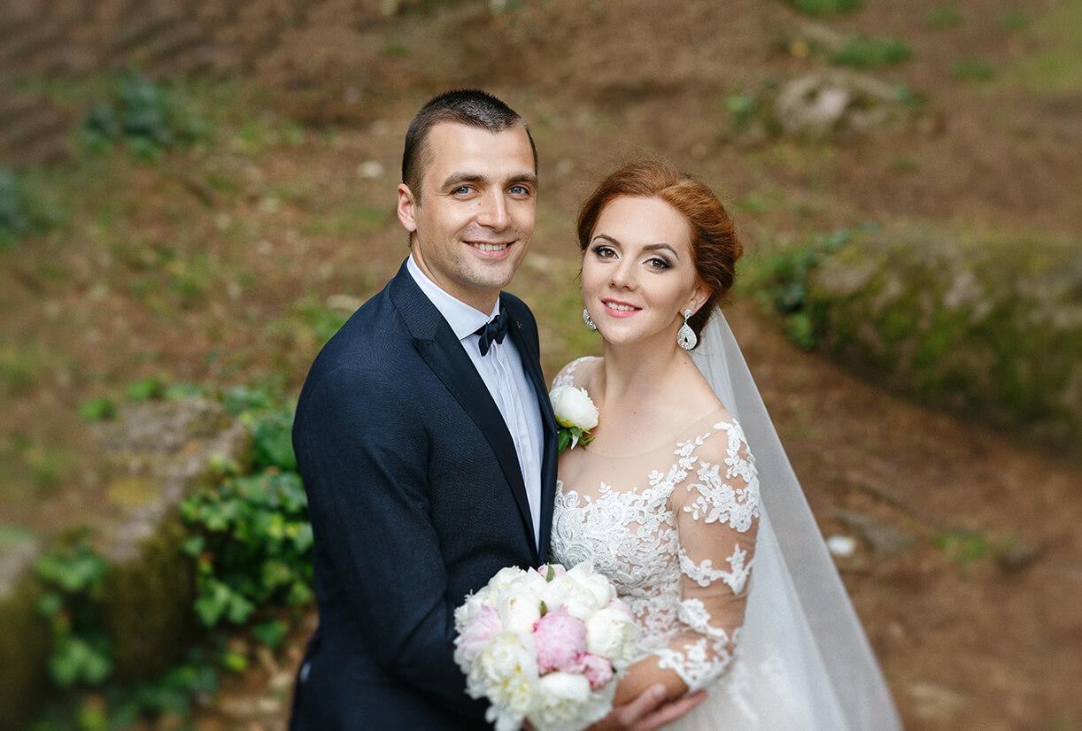 Жених и невеста в свадебном образе с букетом в лесу