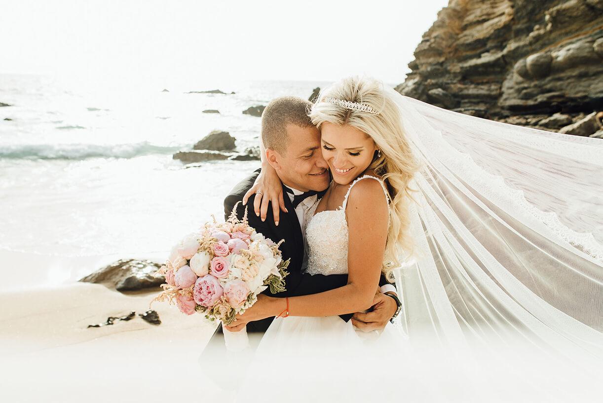 Жених и невеста в свадебных нарядах на фоне моря
