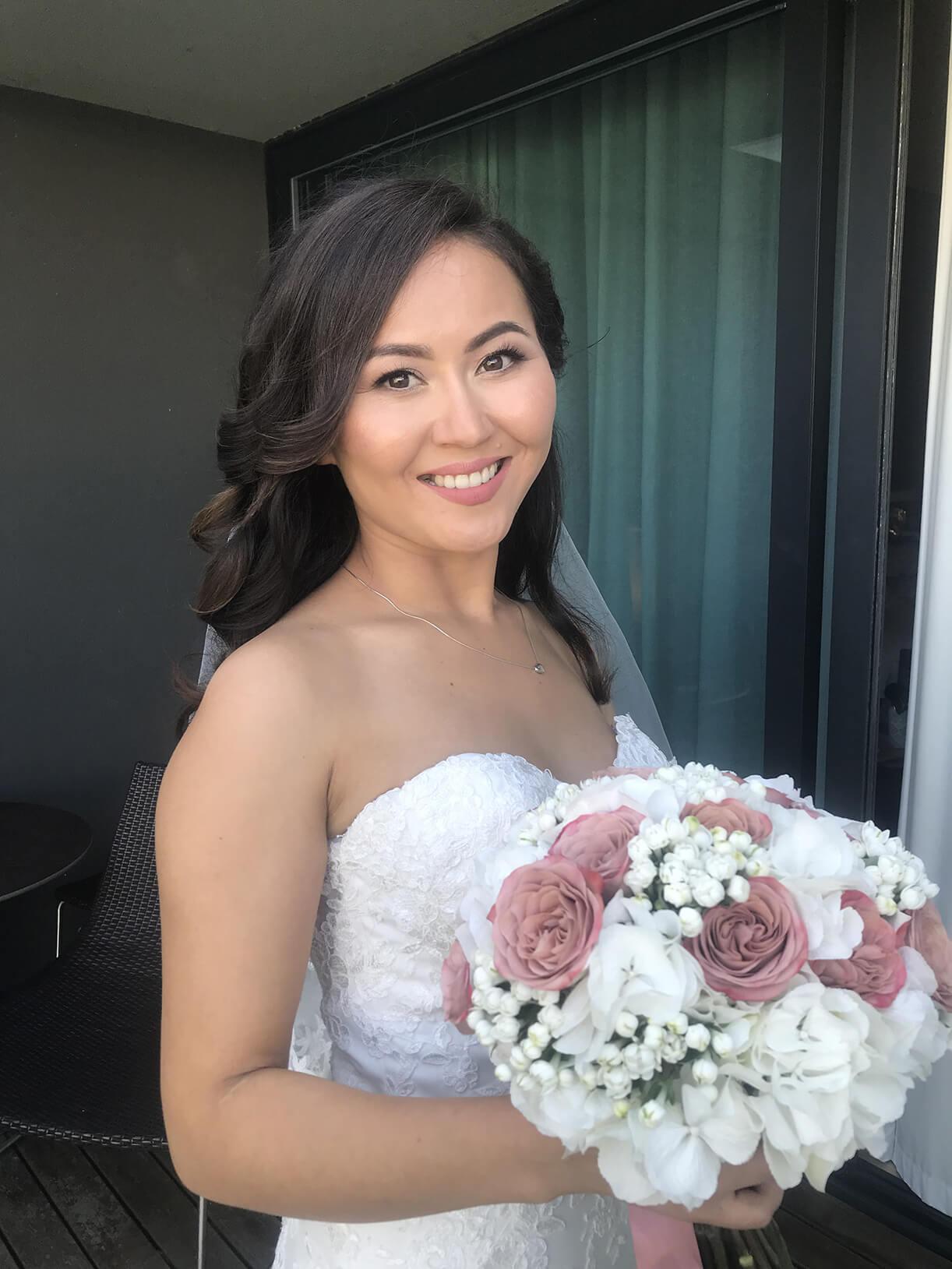 Невеста в свадебном образе на балконе номера в отеле