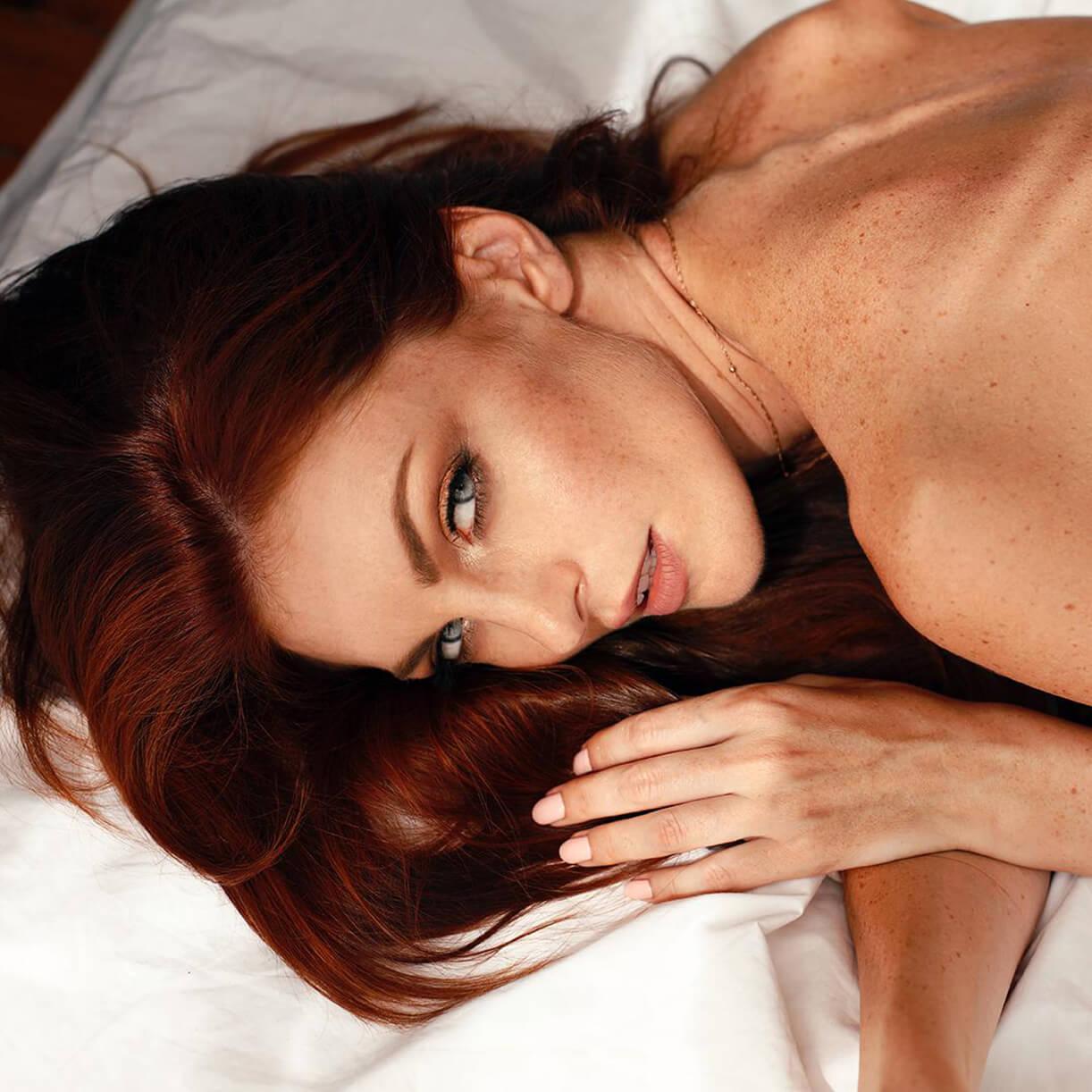Рыжеволосая модель с веснушками на постельном белье. Красивый макияж.
