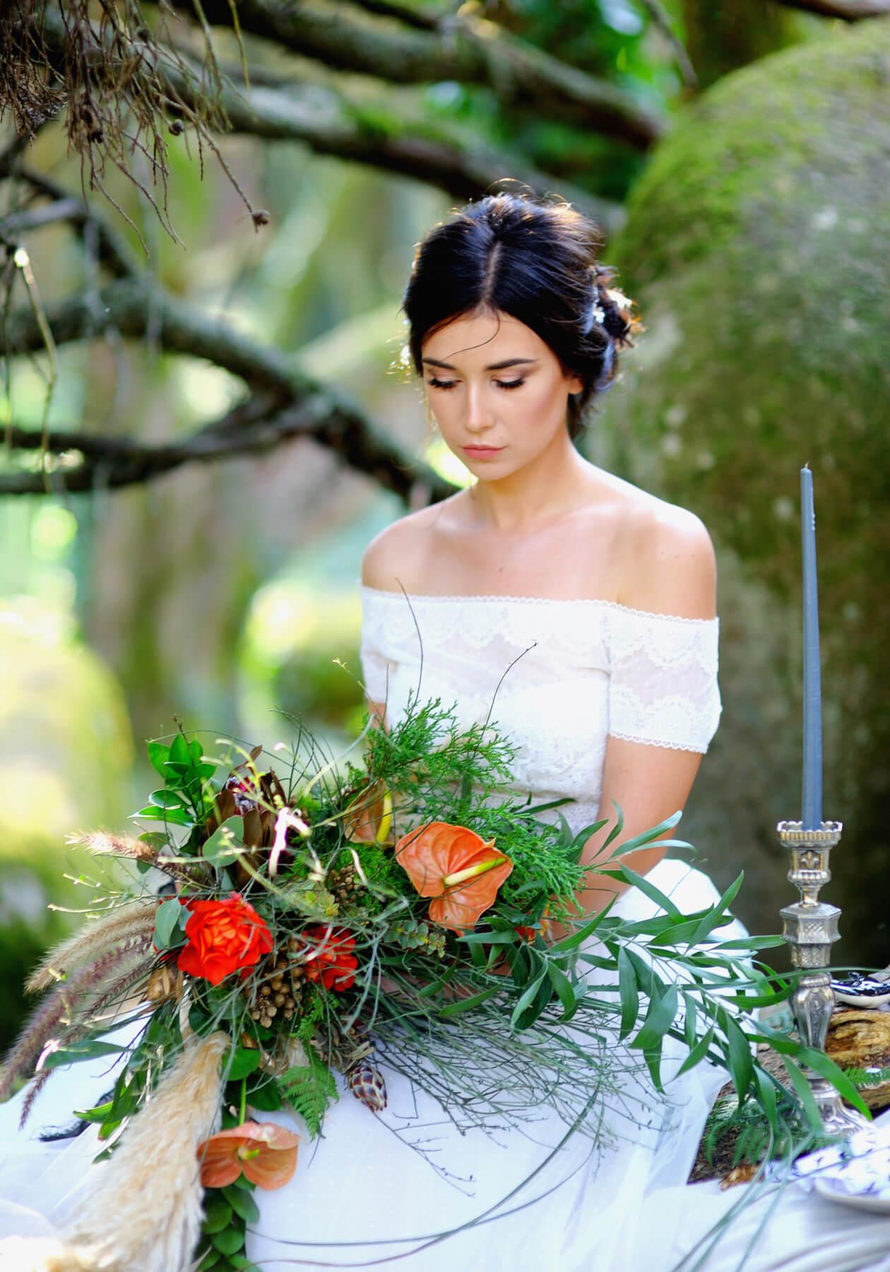 Невеста с букетом, сидящая в лесу