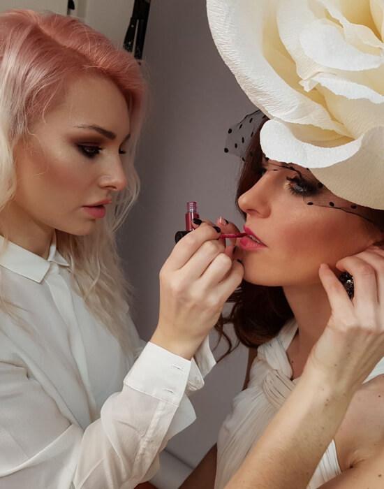 Мастер Ксения Попкова наносит помаду на губы модели