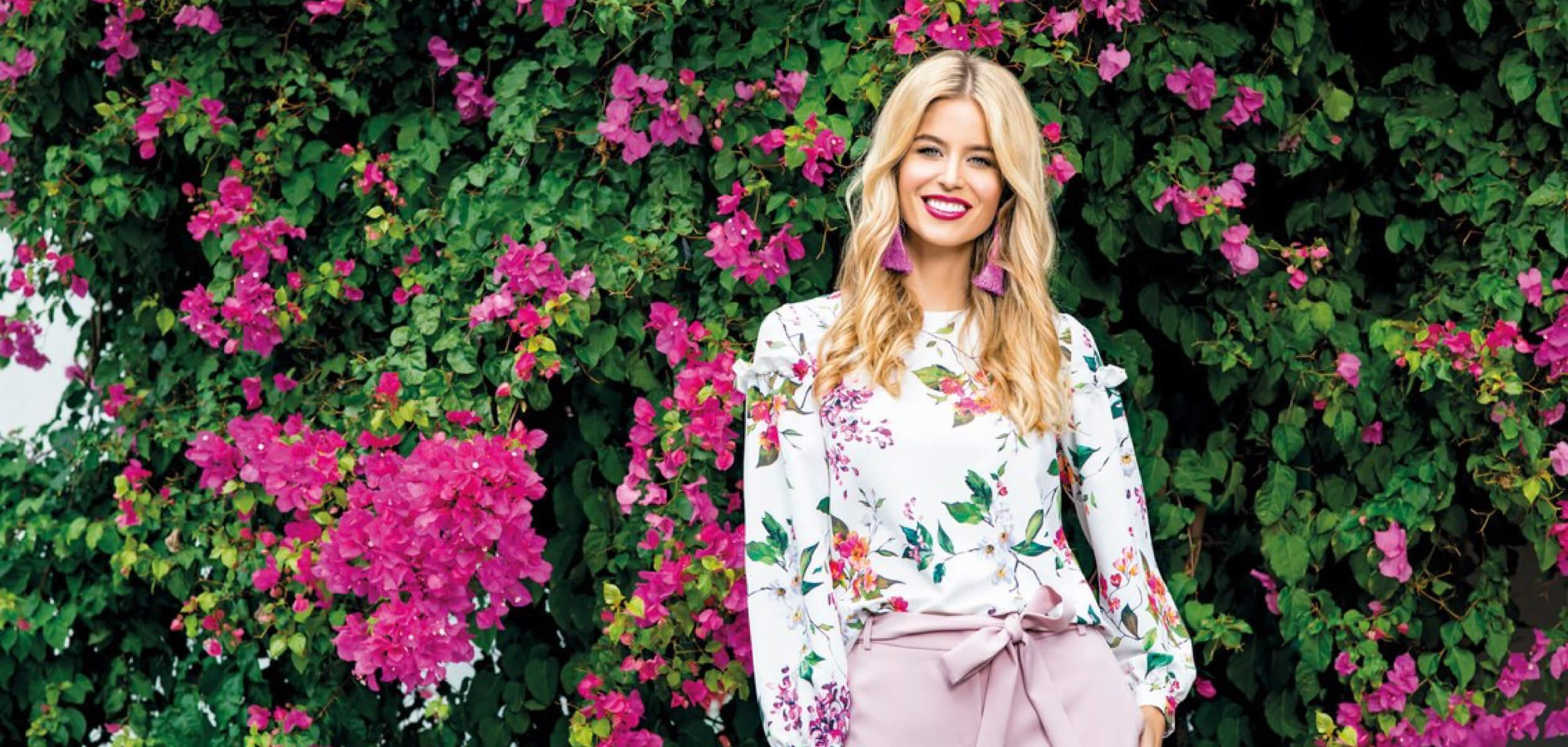 Улыбающаяся блондинка с яркими губами и большими розовыми серьгами на фоне стены с живыми розовыми цветами
