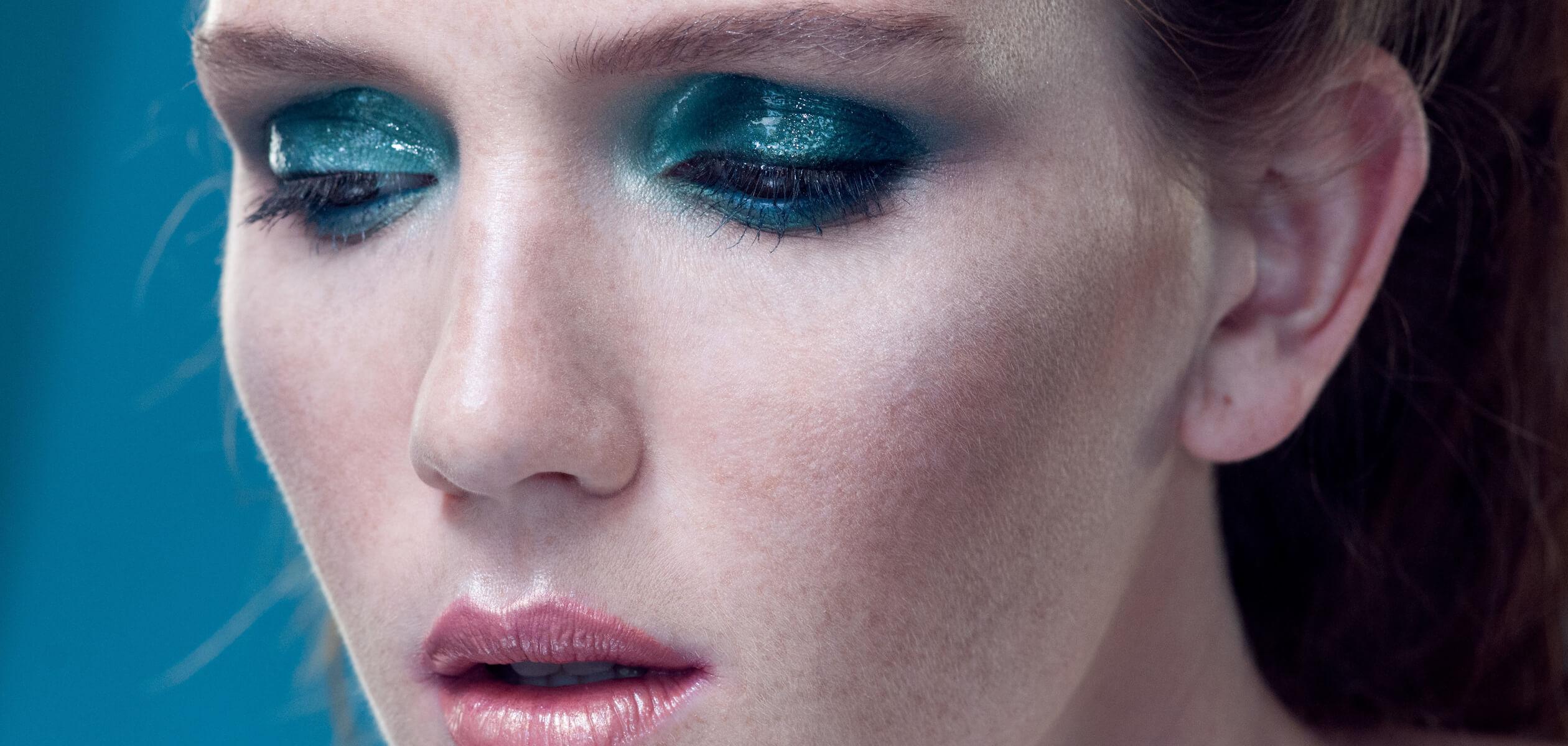 Крупный план лица девушки с голубыми блестящими веками