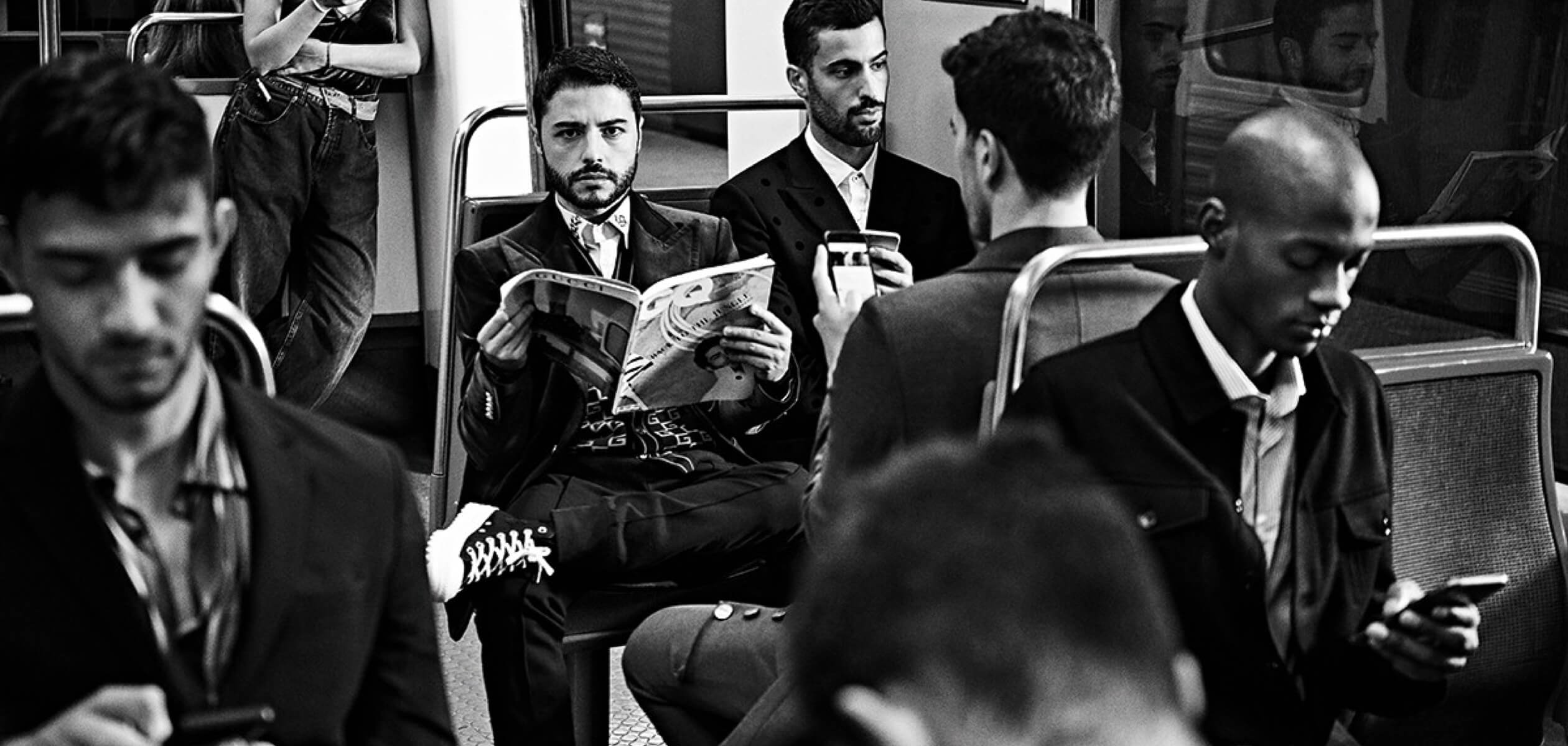 Черно-белое фото мужчин в костюмах, сидящих в метро. У одно в руках журнал GQ