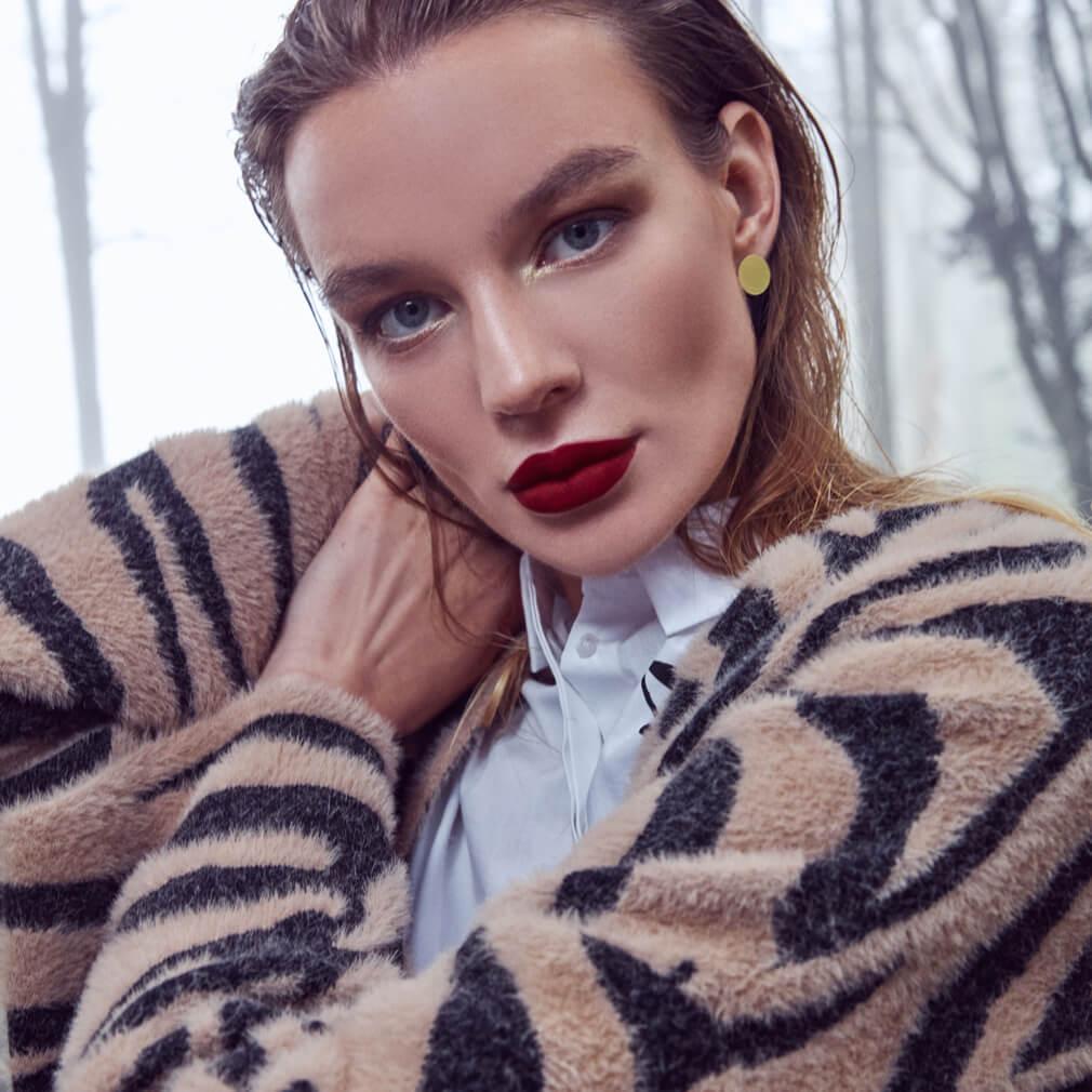 Фотография модели в макияже с красными губами в туманном лесу