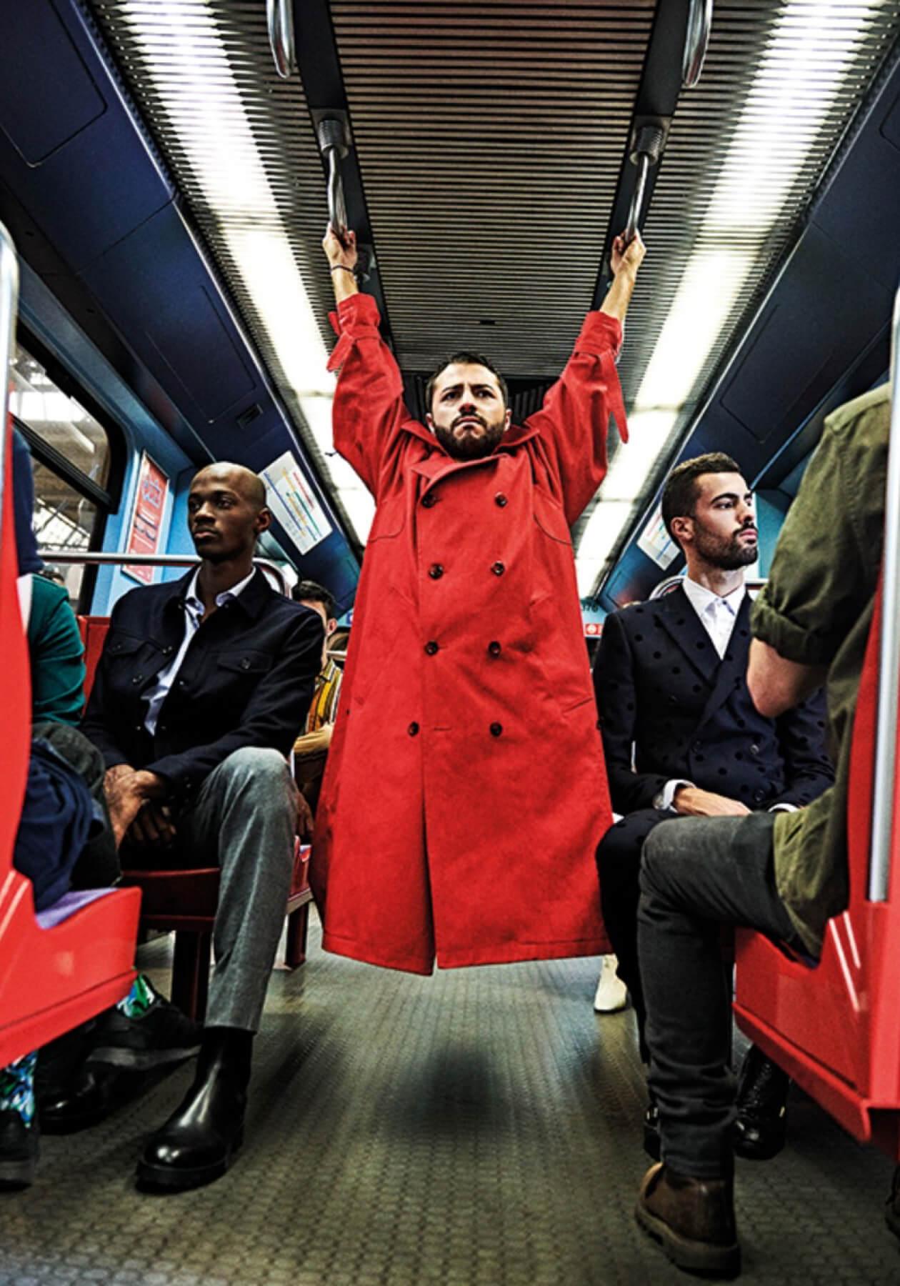 Мужчина в красном плаще висит на поручнях в вагоне метро среди мужчин в костюмах