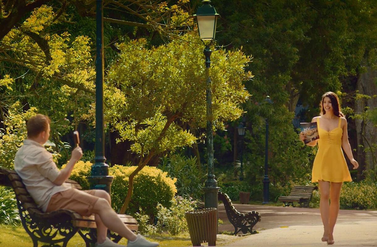 """Кадр из рекламного ролика мороженого """"Каштан"""". Мужчина на скамейке в парке с мороженым и, проходящая рядом девушка"""