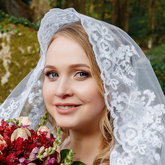 Невеста в фате и с цветами на фоне леса