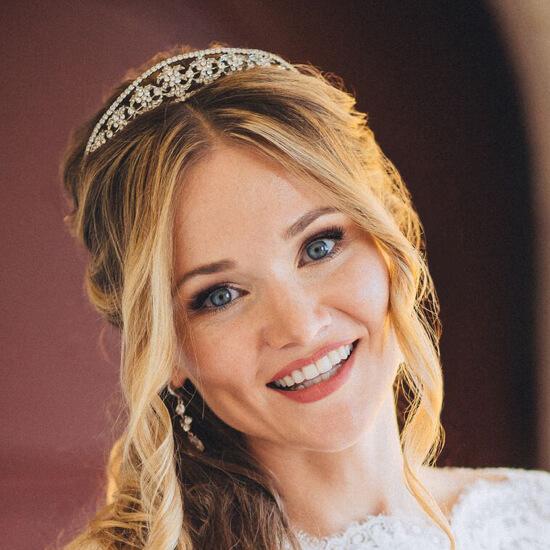 Улыбающаяся невеста с вьющимися волосами, тиарой и свадебным макияжем