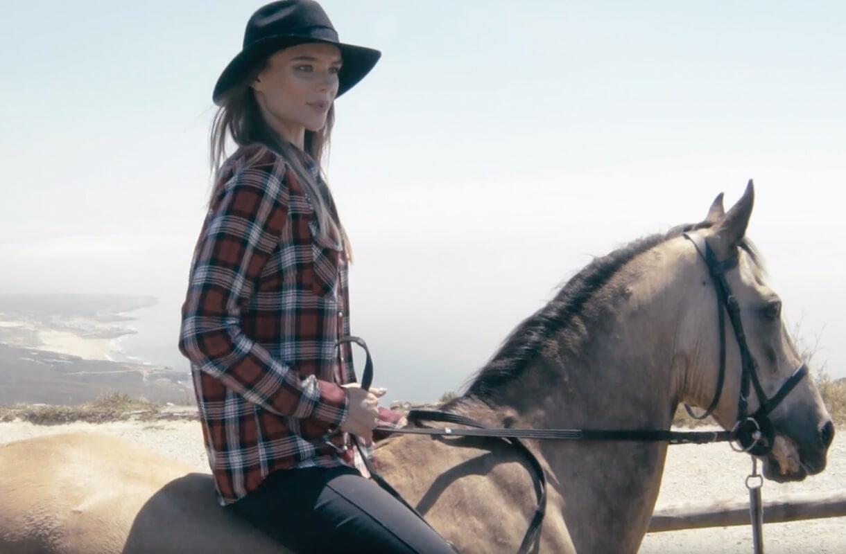 Кадр из рекламы ZARINA с девушкой в черной шляпе на лошади