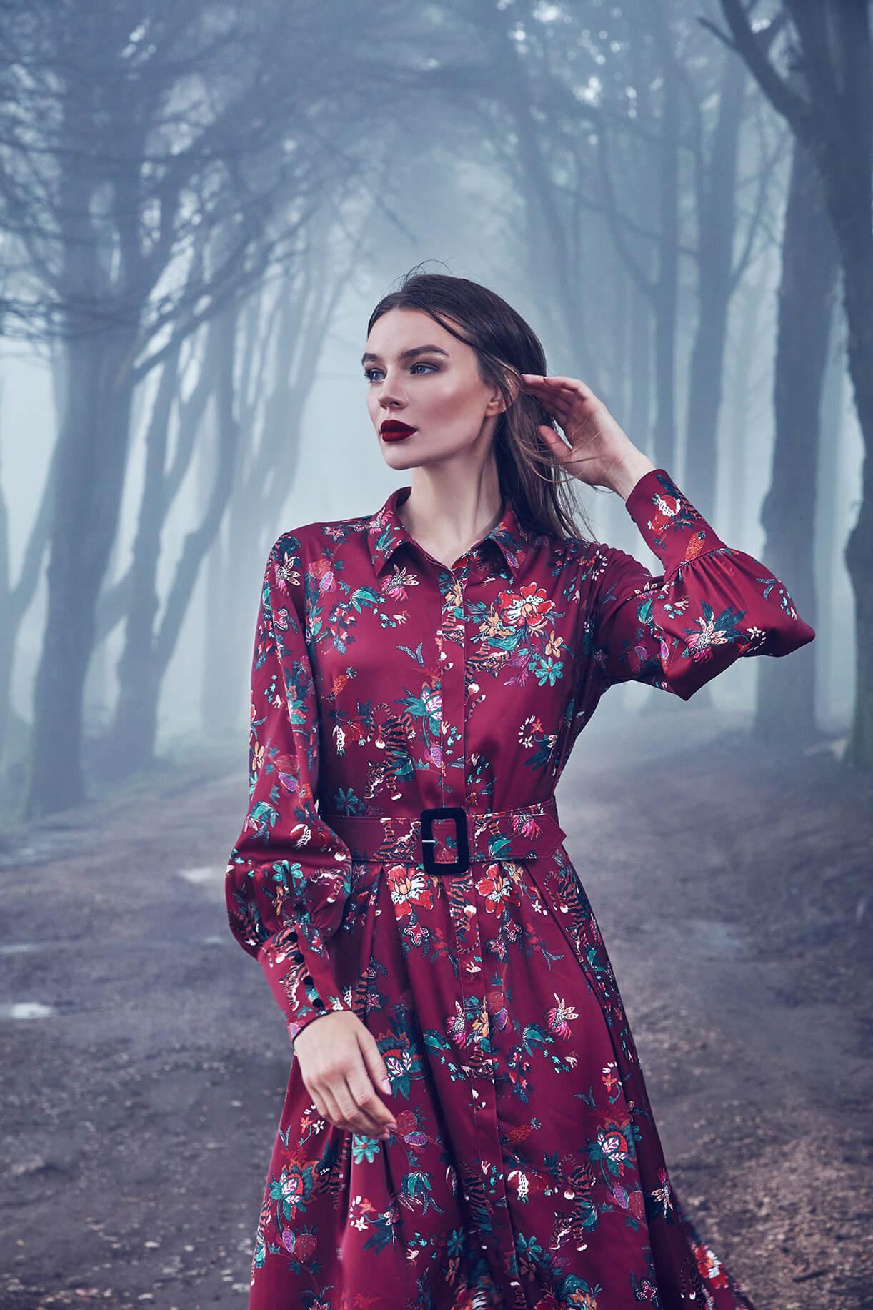 Модель в бордовом платье с цветочным принтом в туманном лесу