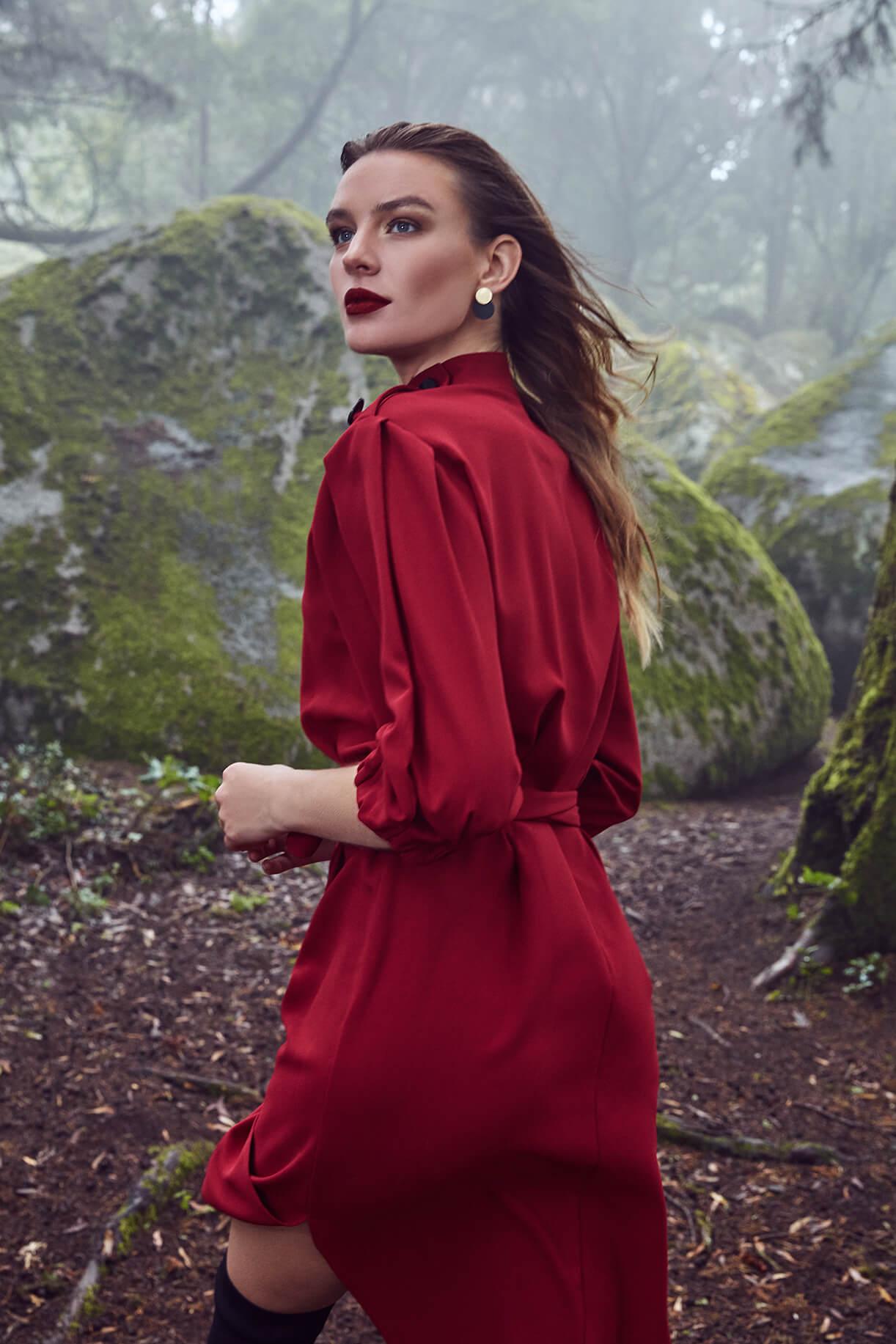 Модель в красном платье и с ярким макияжем в туманном лесу