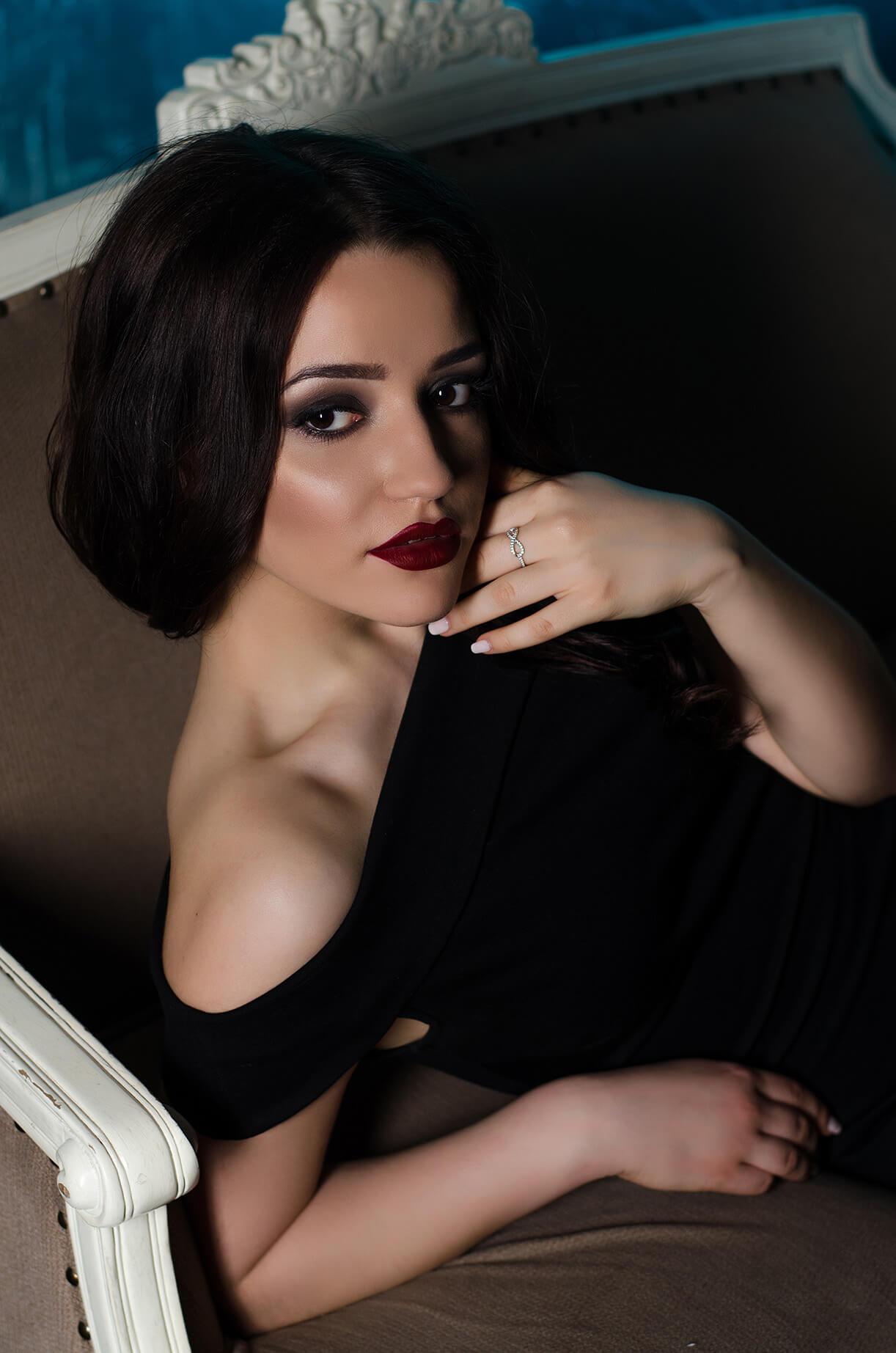 Девушка в черном платье на винтажной софе
