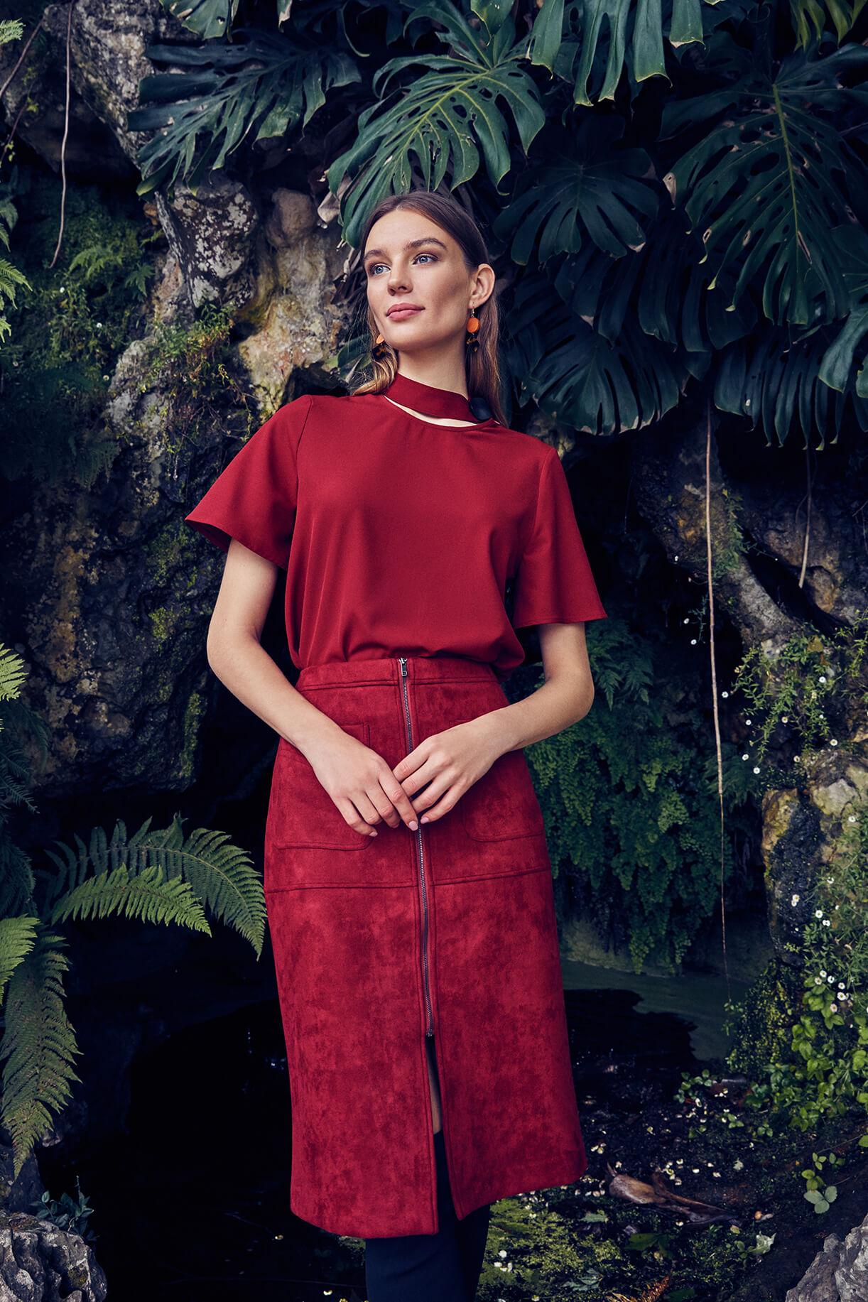 Модель в красной блузке и красной юбке на фоне тропического леса