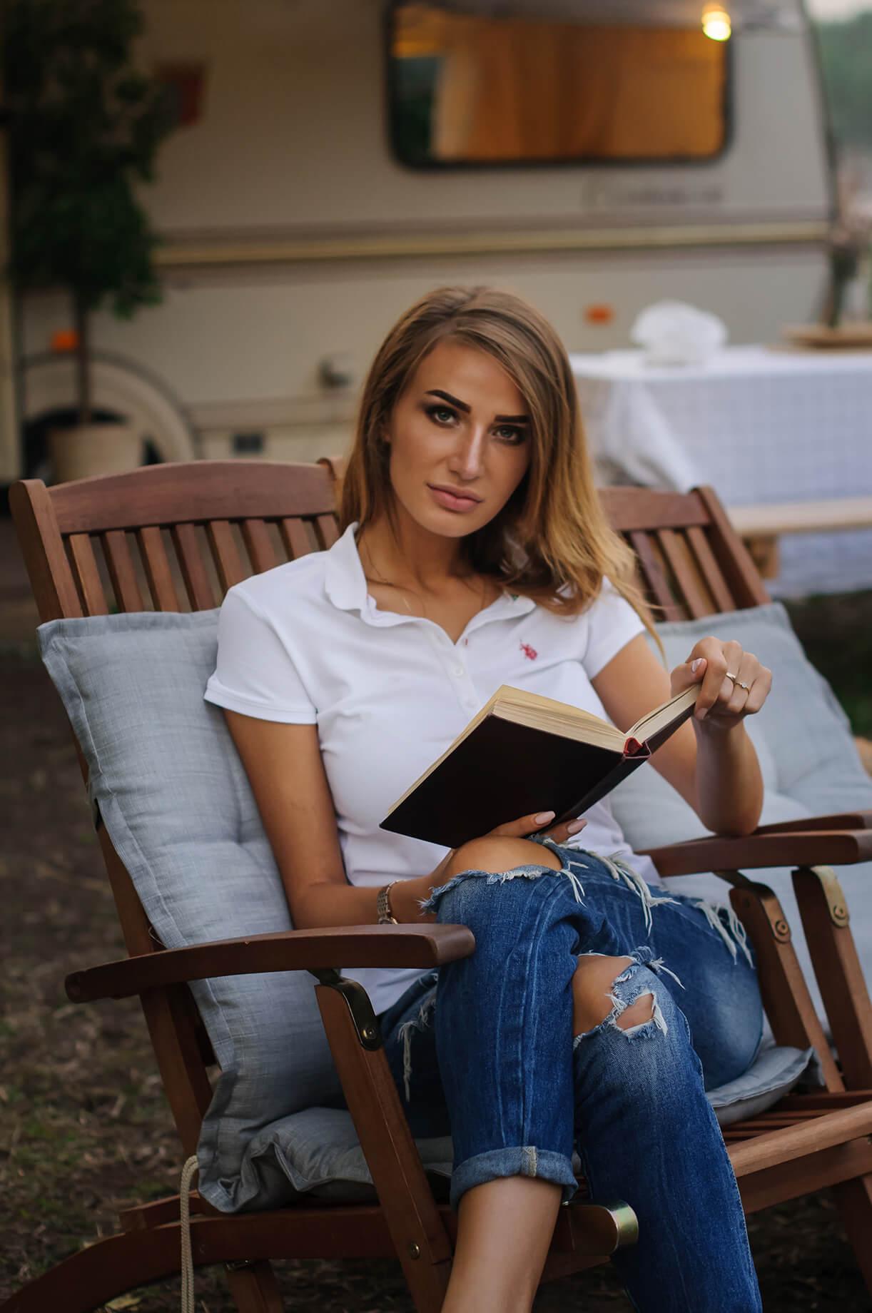 Девушка с макияжем читает книгу в кресле на природе
