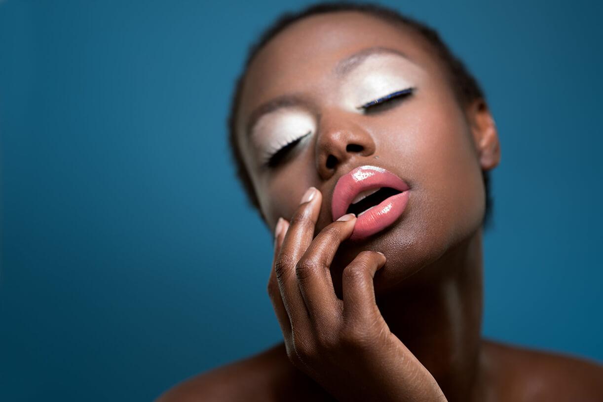 Темнокожая модель с макияжем на голубом фоне