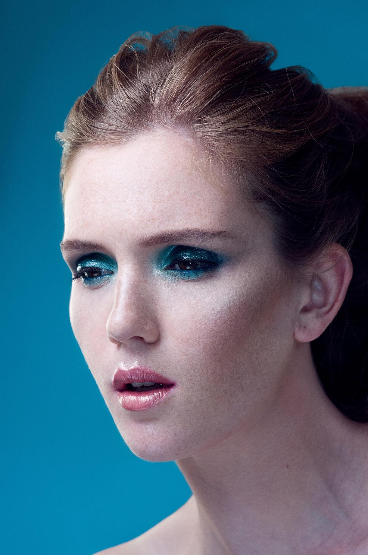 Модель с голубым макияжем вокруг глаз на голубом фоне