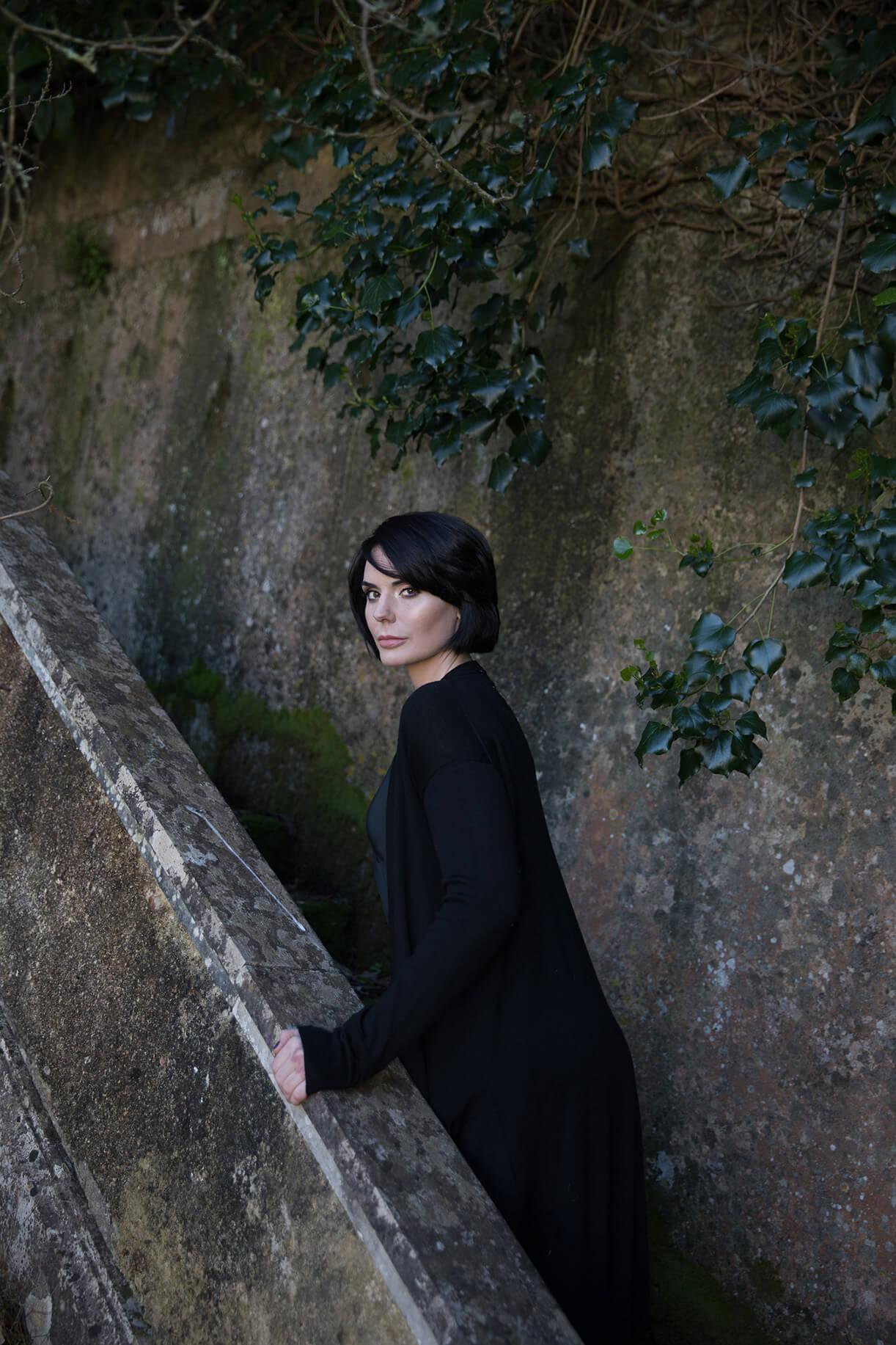 Девушка с макияжем на фоне каменной стены