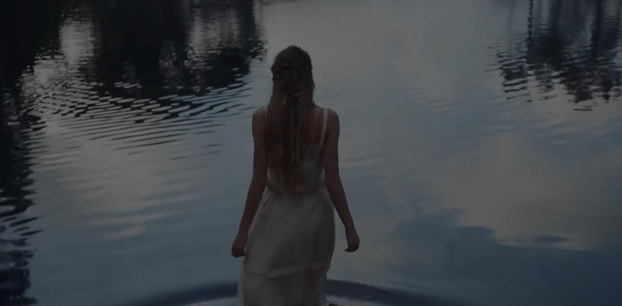 Кадр из видео для EDP с девушкой в светлом платье, входящей в воду