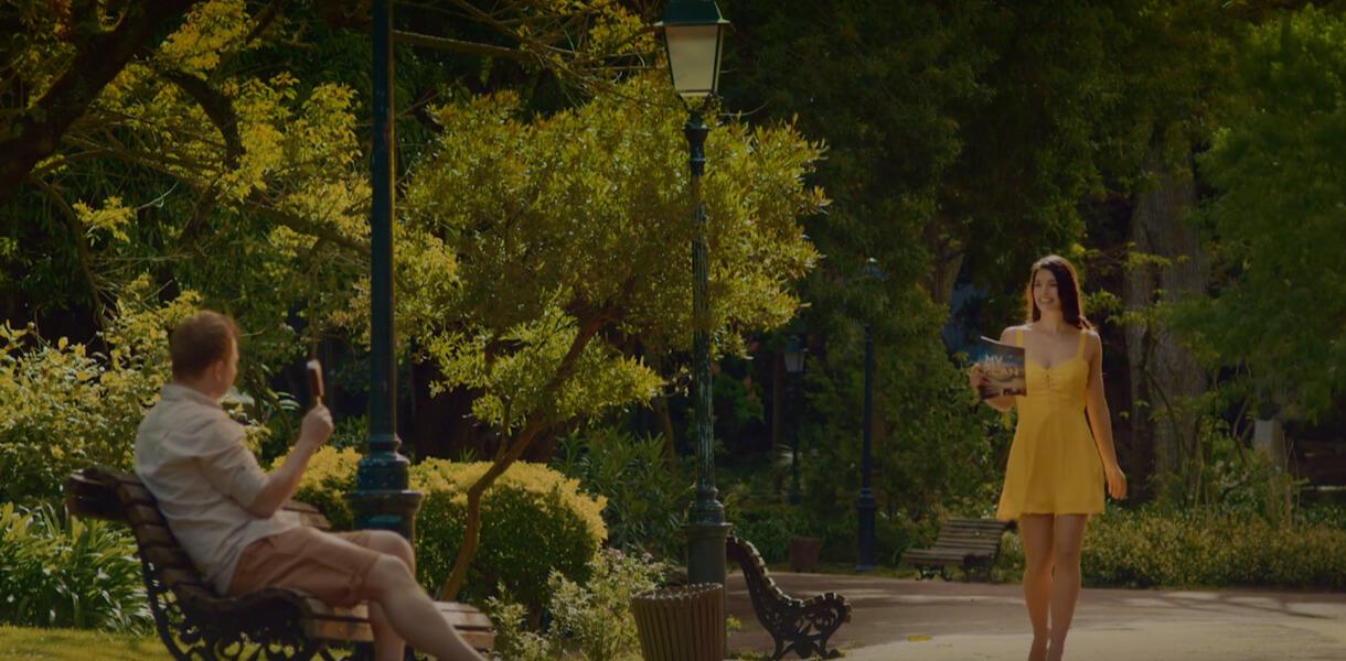 """Кадр из ролика мороженого """"Каштан"""" с мужчиной с мороженым в руке и проходящей девушкой в парке"""