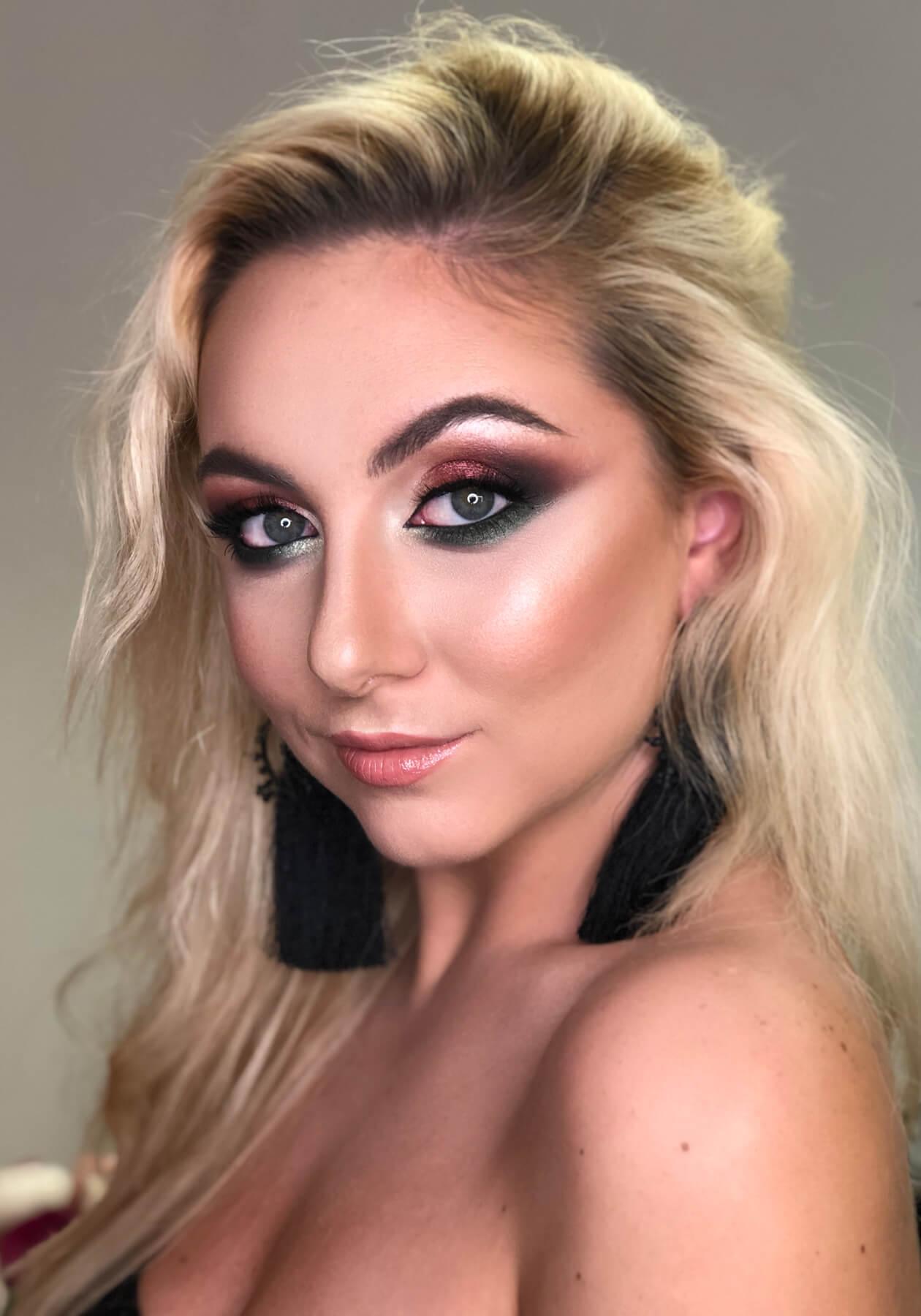 Блондинка с вечерним макияжем и большими черными серьгами смотрит в камеру