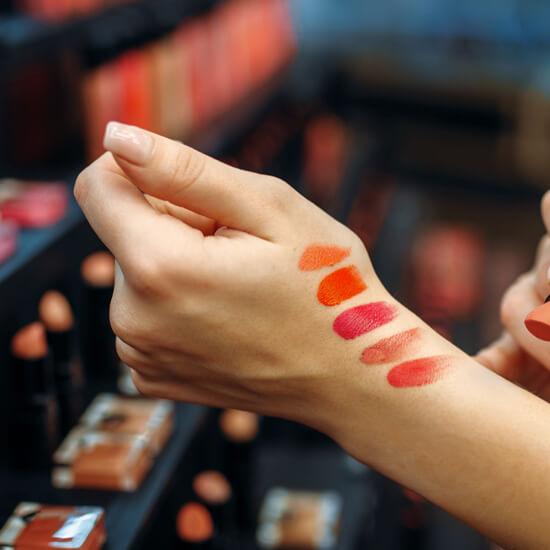 Женская рука с мазками губной помады на фоне прилавков в магазине