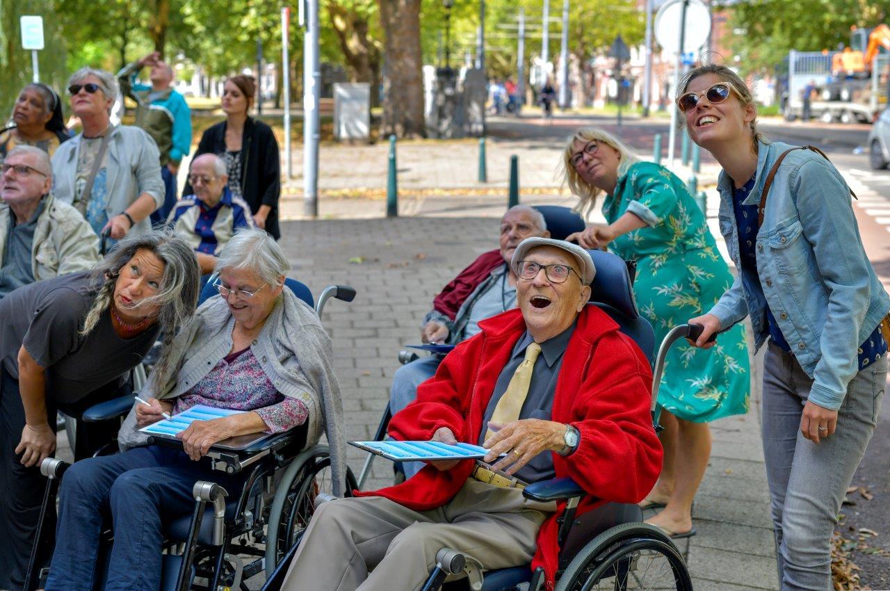 Kunstenaar Misja Immink tijdens een Gelukswandeling met een groep ouderen in rolstoel en vrijwilligers.