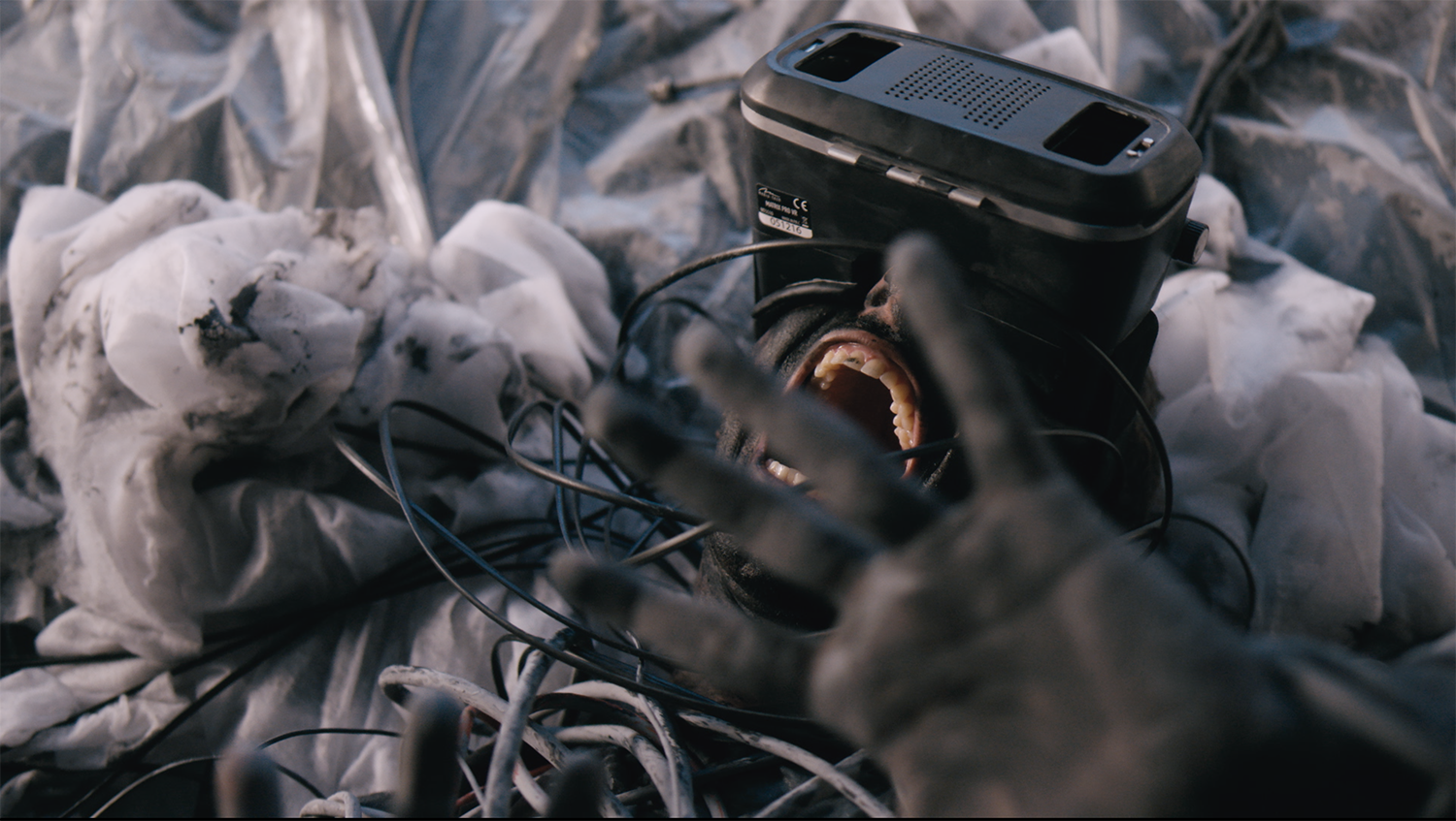 """Official still from music video """"Feel Complete"""", a picture of a man with VR glasses screaming."""