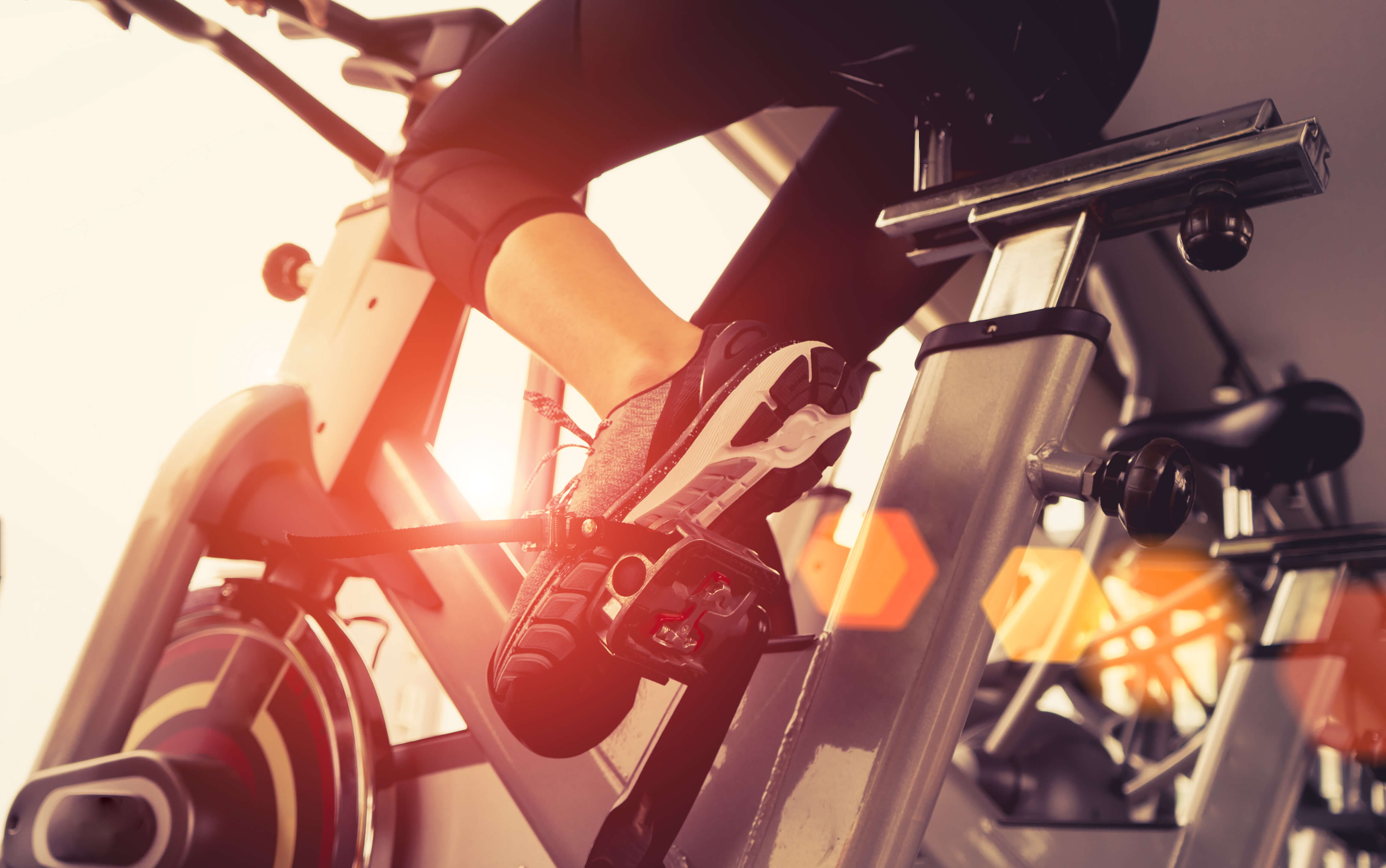 Girl riding stationary bike in gym